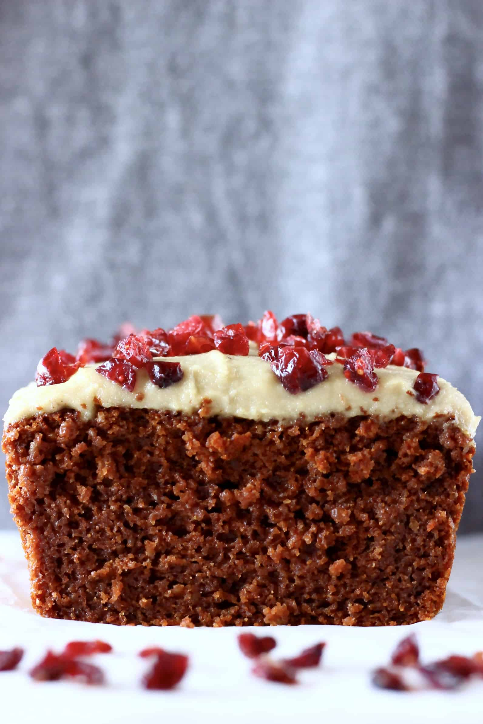 Sliced gluten-free vegan gingerbread loaf cake topped with white frosting and dried cranberries