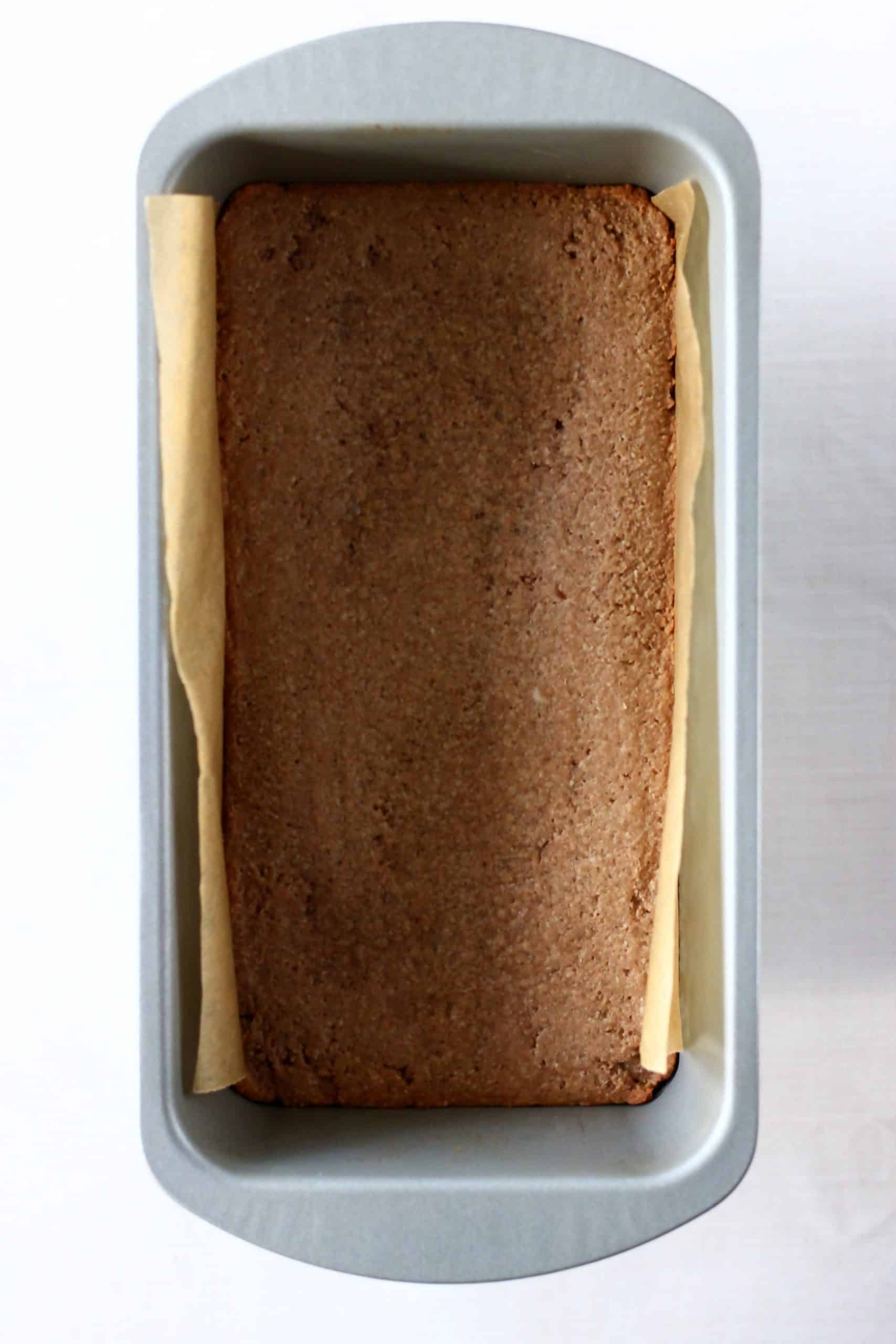 Baked gluten-free vegan gingerbread cookie bars in a loaf tin lined with baking paper