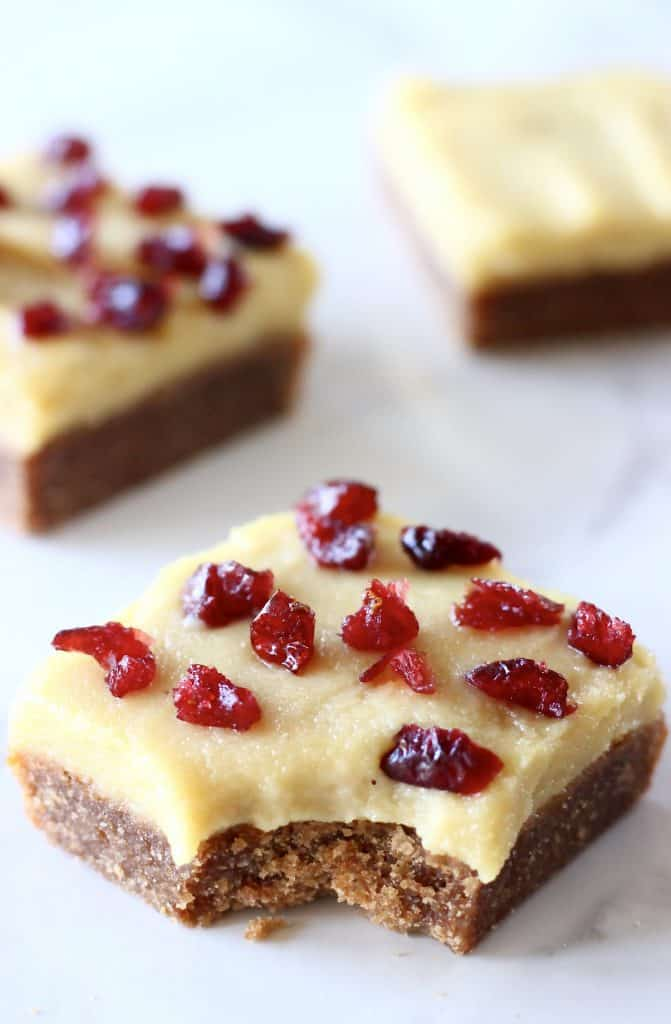 Three gingerbread cookie bars with frosting and dried cranberries with a bite taken out of one