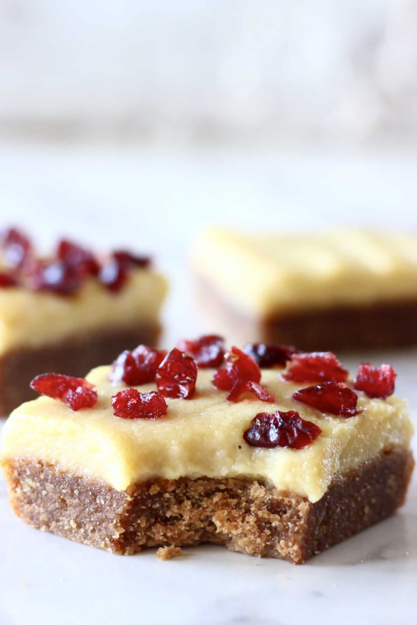 Three gluten-free vegan gingerbread cookie bars with frosting and dried cranberries with a bite taken out of one