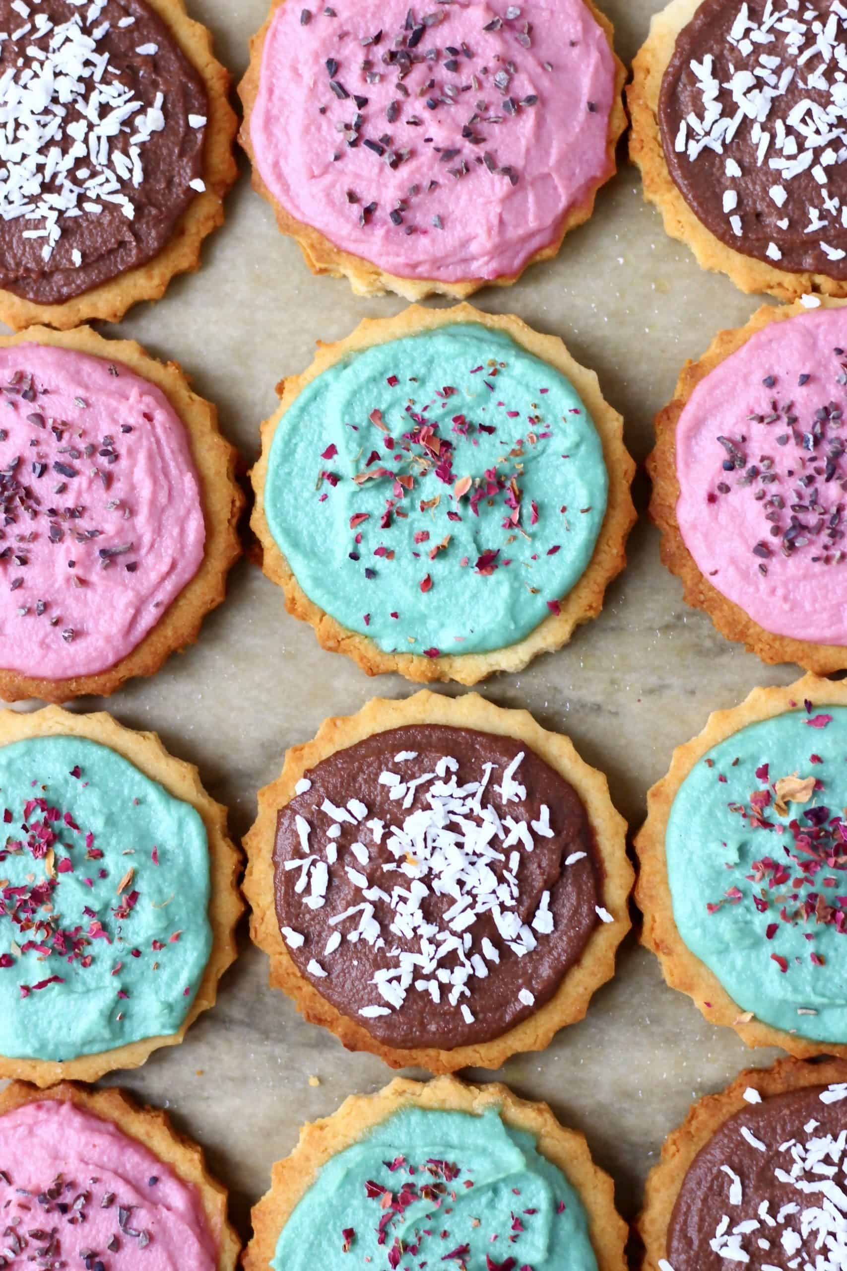 Twelve circular sugar cookies topped with different coloured frosting and sprinkles on a sheet of brown baking paper
