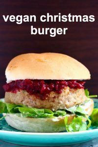 Vegan Christmas burger with cranberry sauce and rocket against a dark brown background