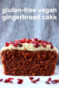 Sliced gingerbread loaf cake topped with white frosting and dried cranberries