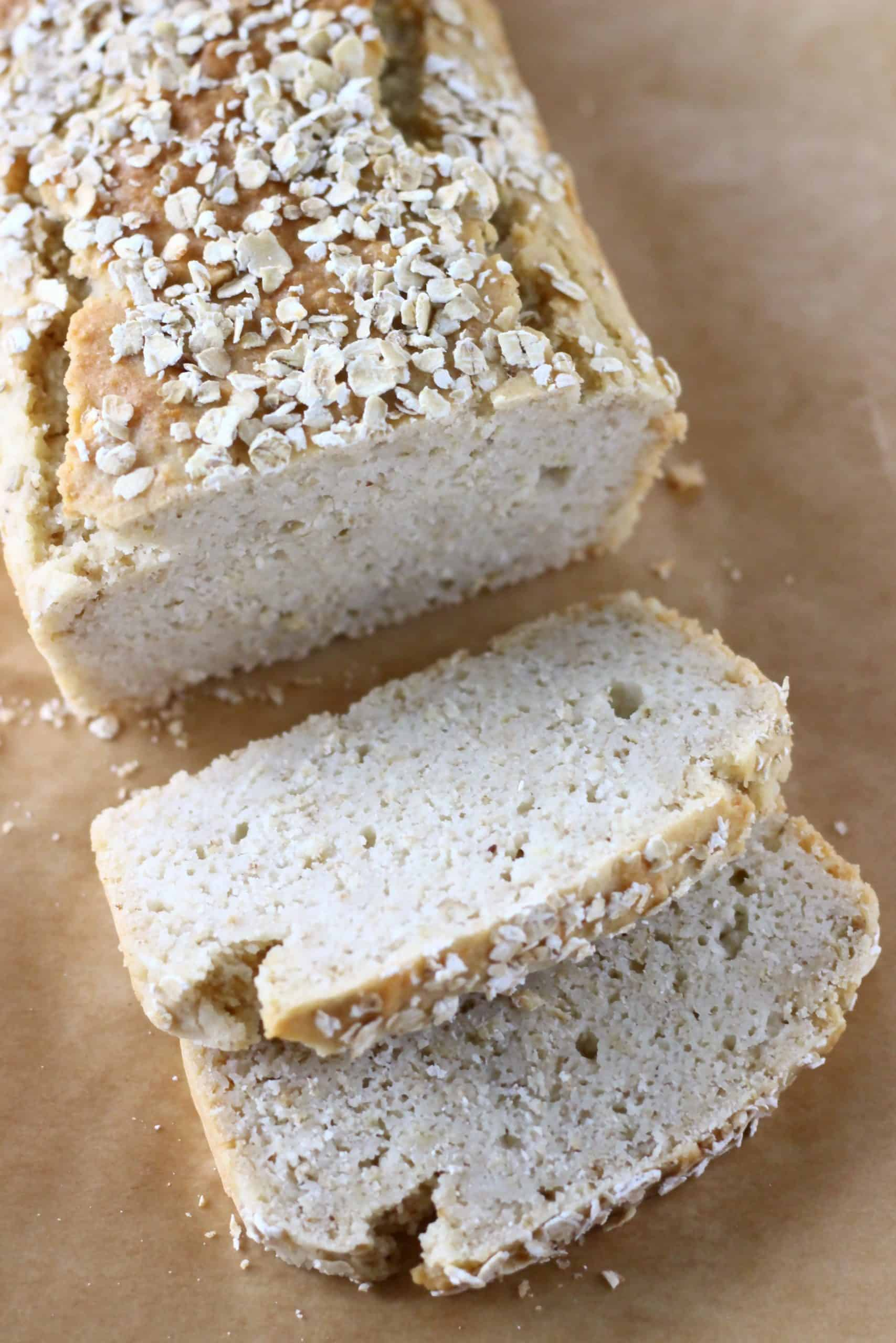 A loaf of brown bread topped with oats with two slices on the side against a sheet of brown baking paper