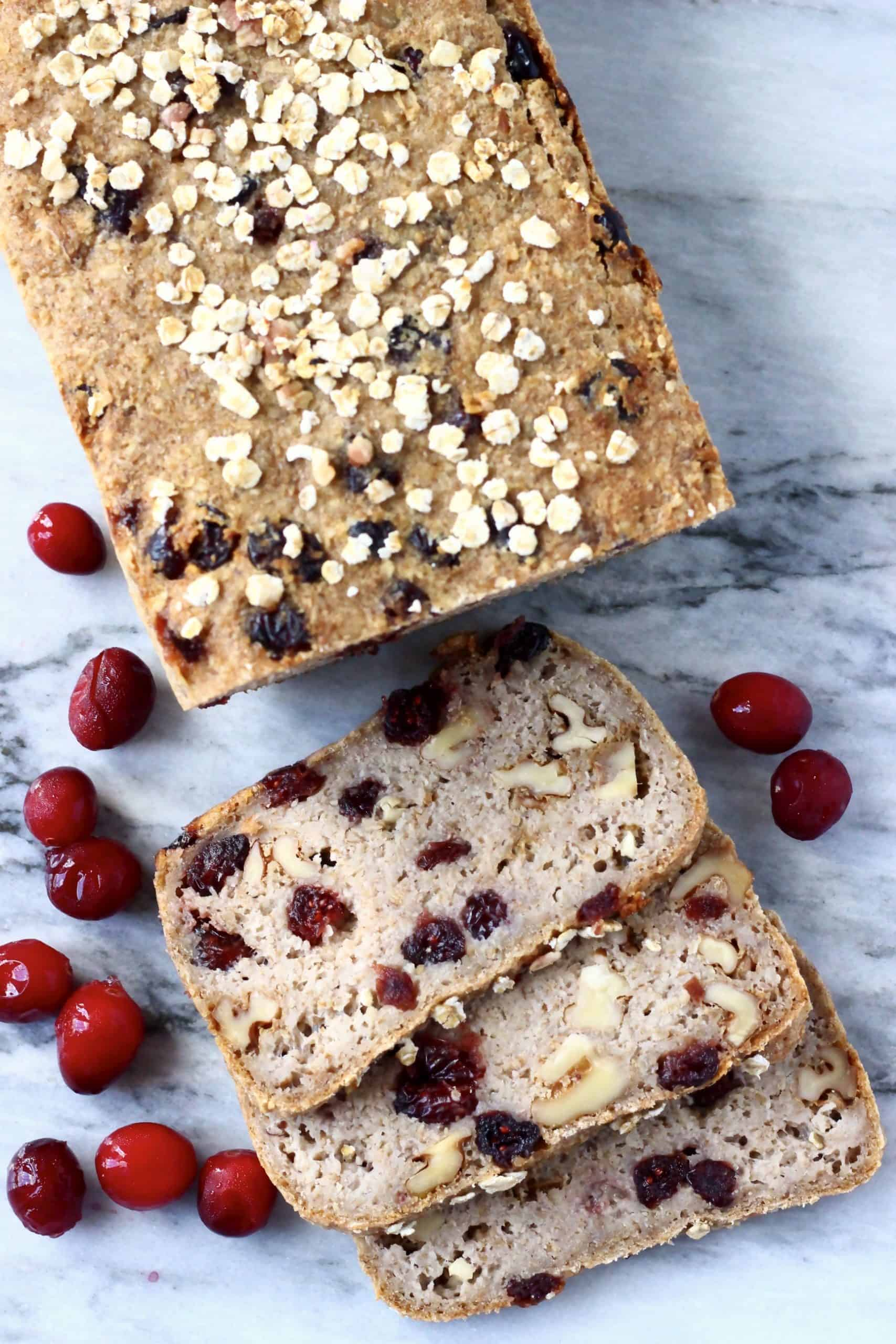 A loaf of brown bread with cranberries sprinkled with oats with three slices cut from it on a marble background scattered with fresh cranberries