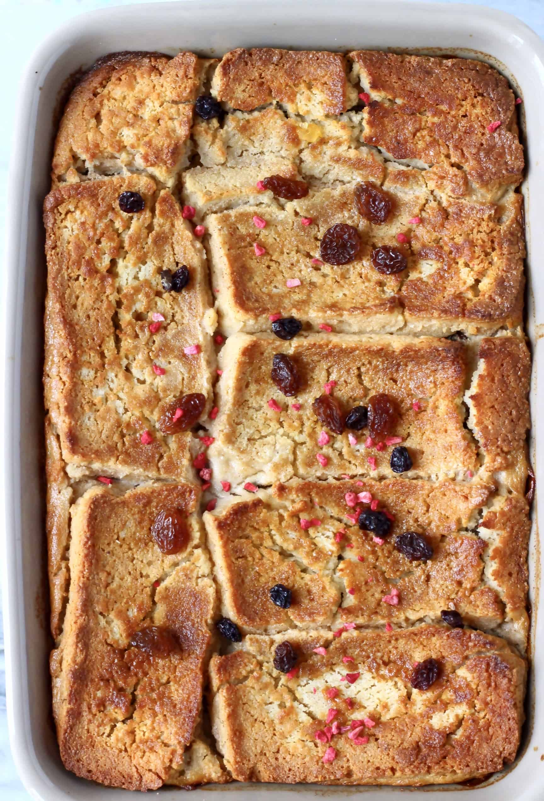 Bread pudding in a grey rectangular baking dish sprinkled with raisins