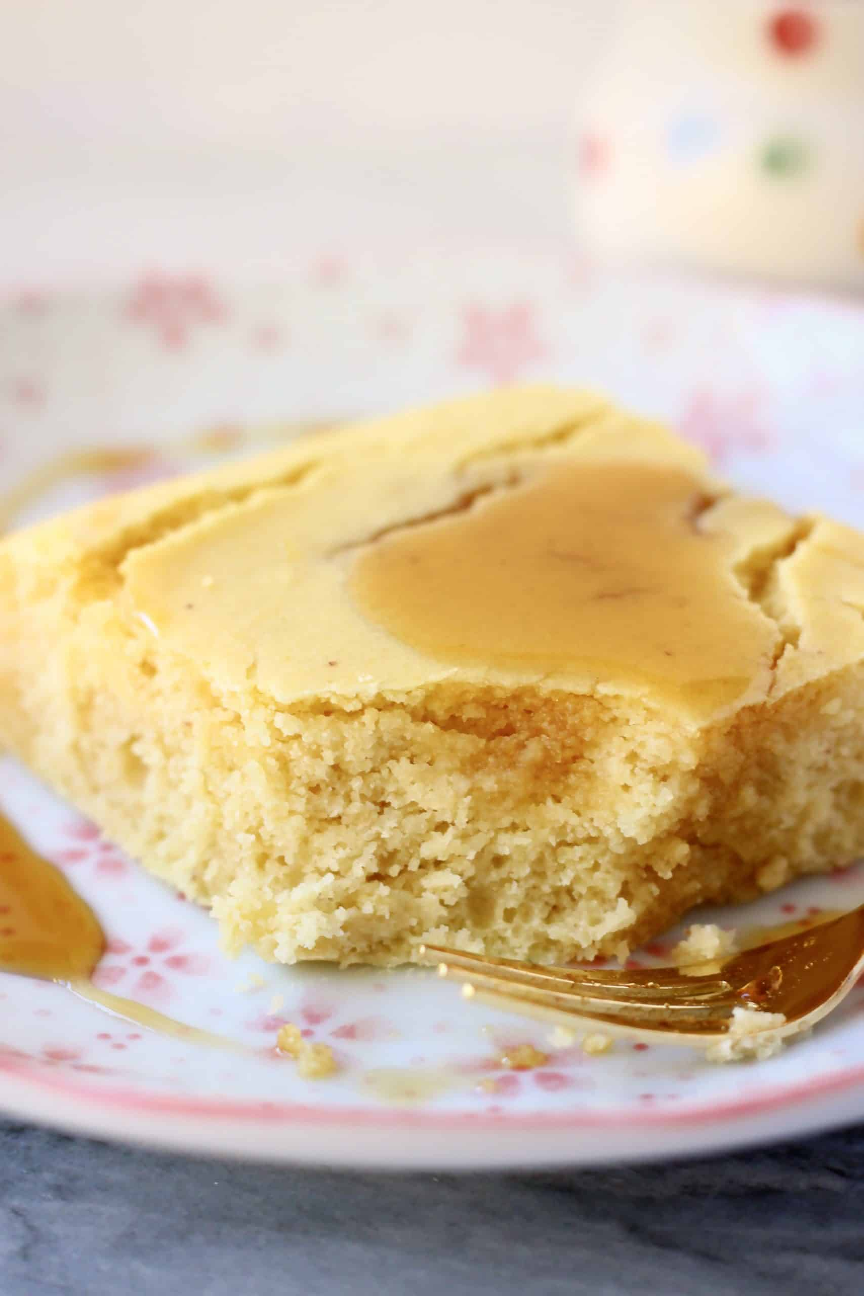 A square of cornbread with a mouthful taken out of it and maple syrup poured on top