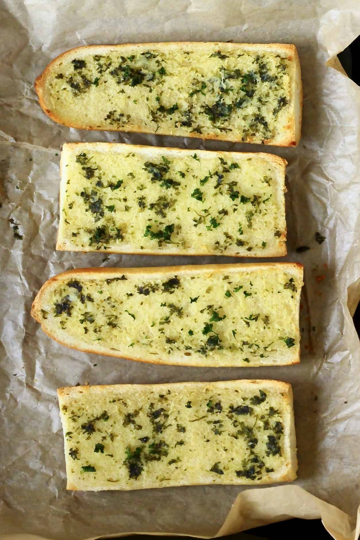 Four pieces of garlic bread on a sheet of brown baking paper