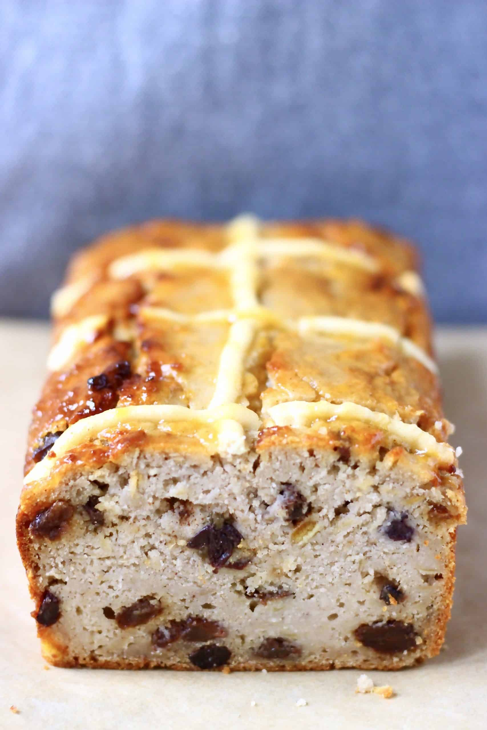 Hot cross bun loaf on a sheet of brown baking paper against a grey background