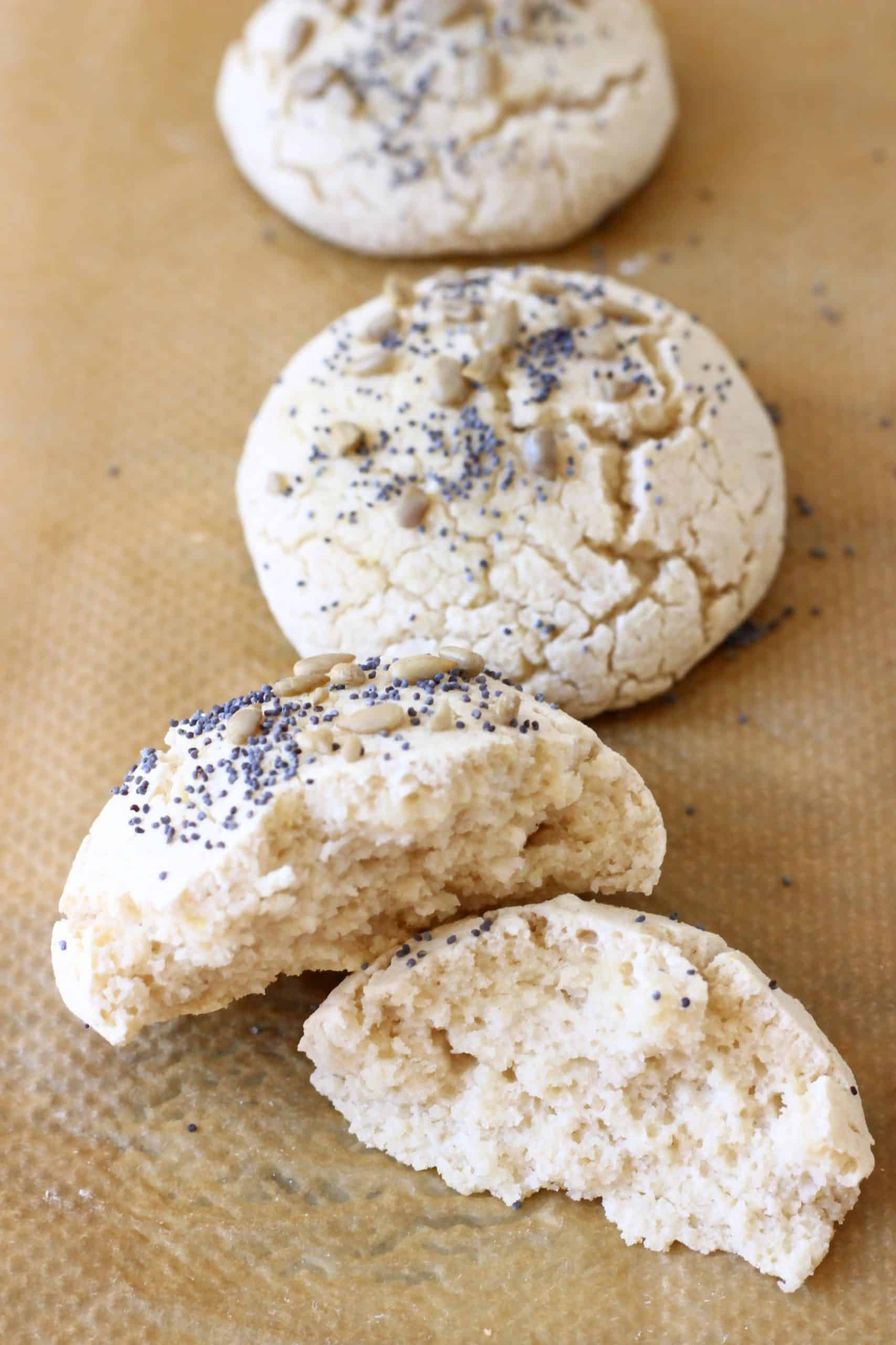 Three bread rolls topped with seeds, one torn in half