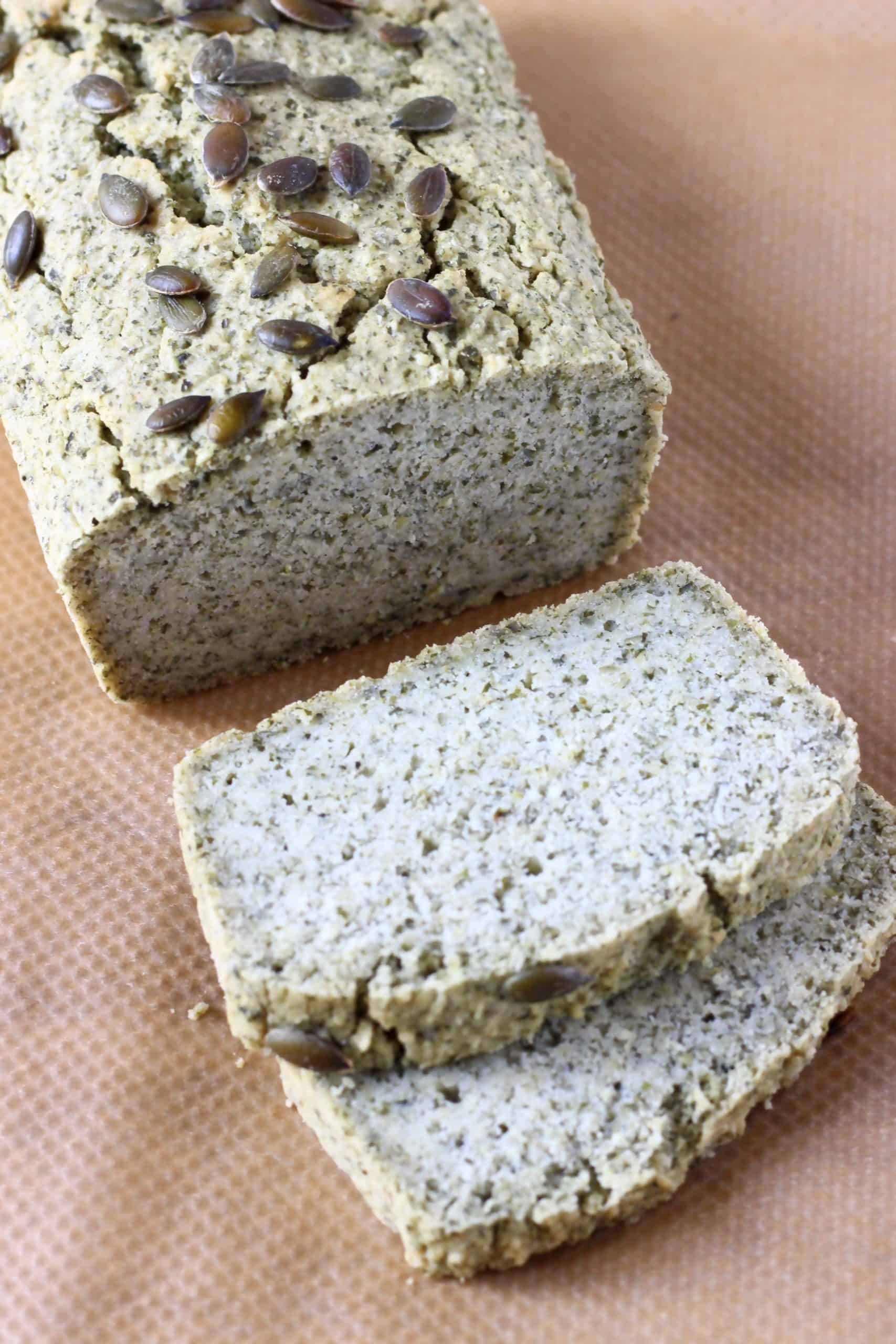 A loaf of pumpkin seed bread with two slices next to it