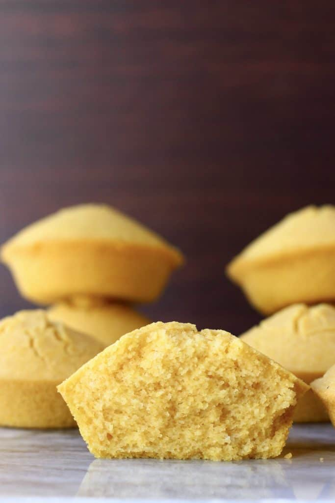 Six cornbread muffins with one cut in half on a marble slab against a dark brown background