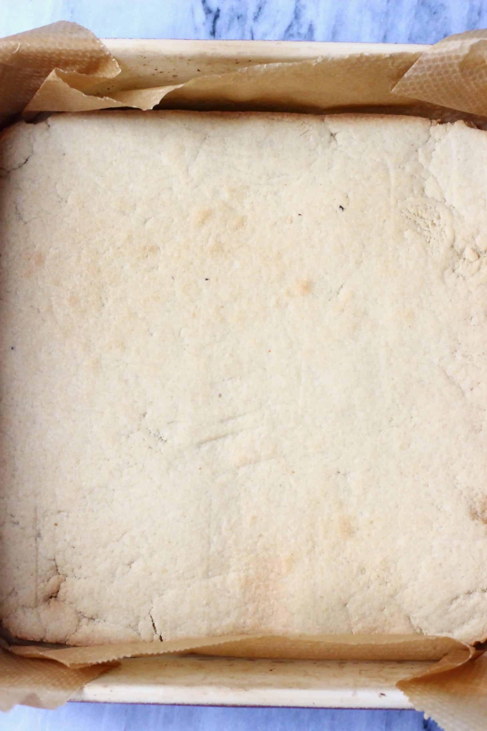 Baked gluten-free vegan crumble bar base in a square baking tin
