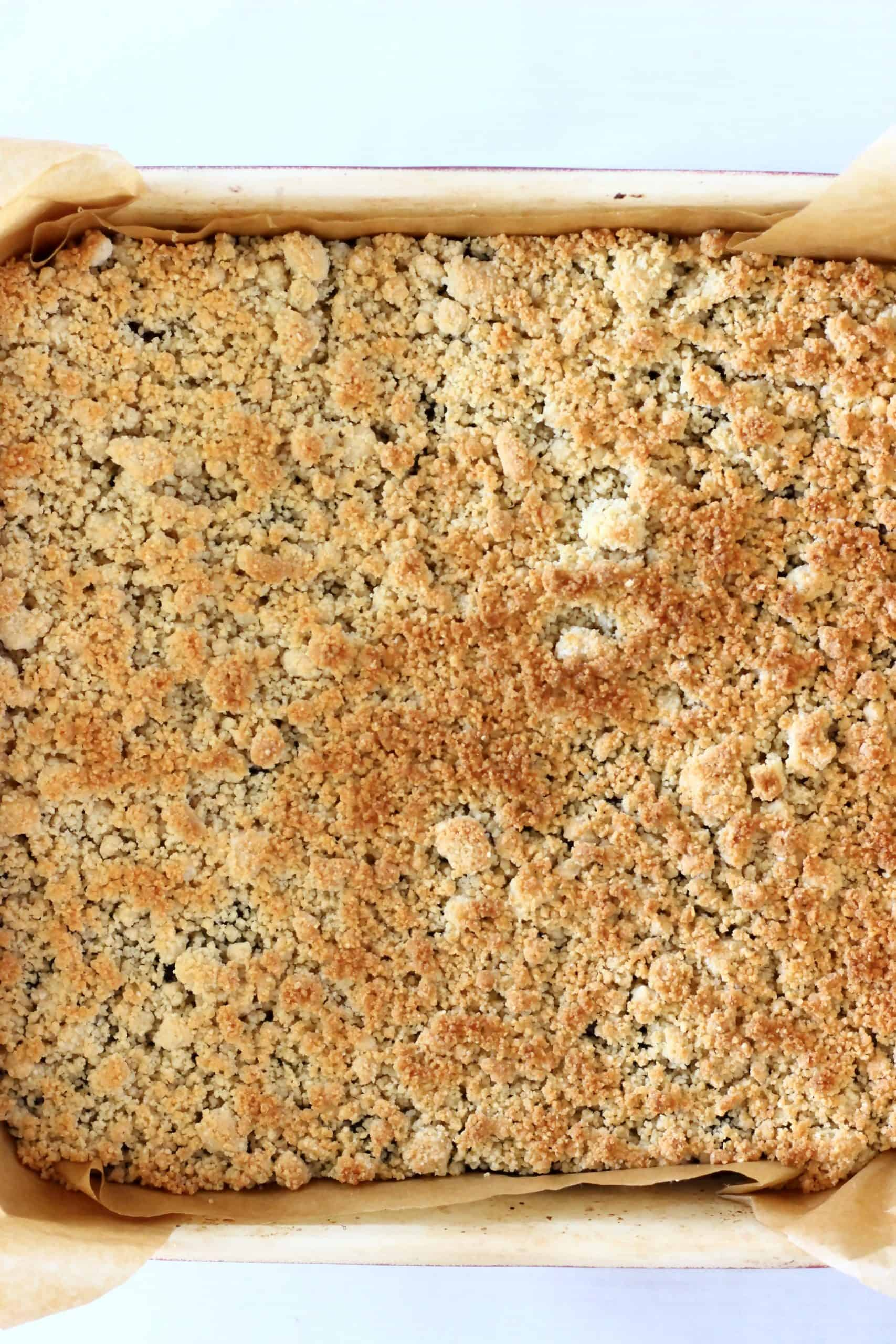 Baked gluten-free vegan blueberry crumble bars in a square baking tin