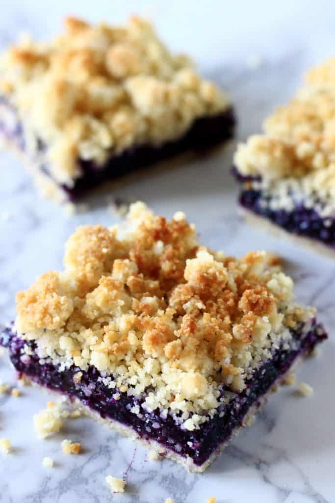 Three blueberry crumble bar squares against a marble background