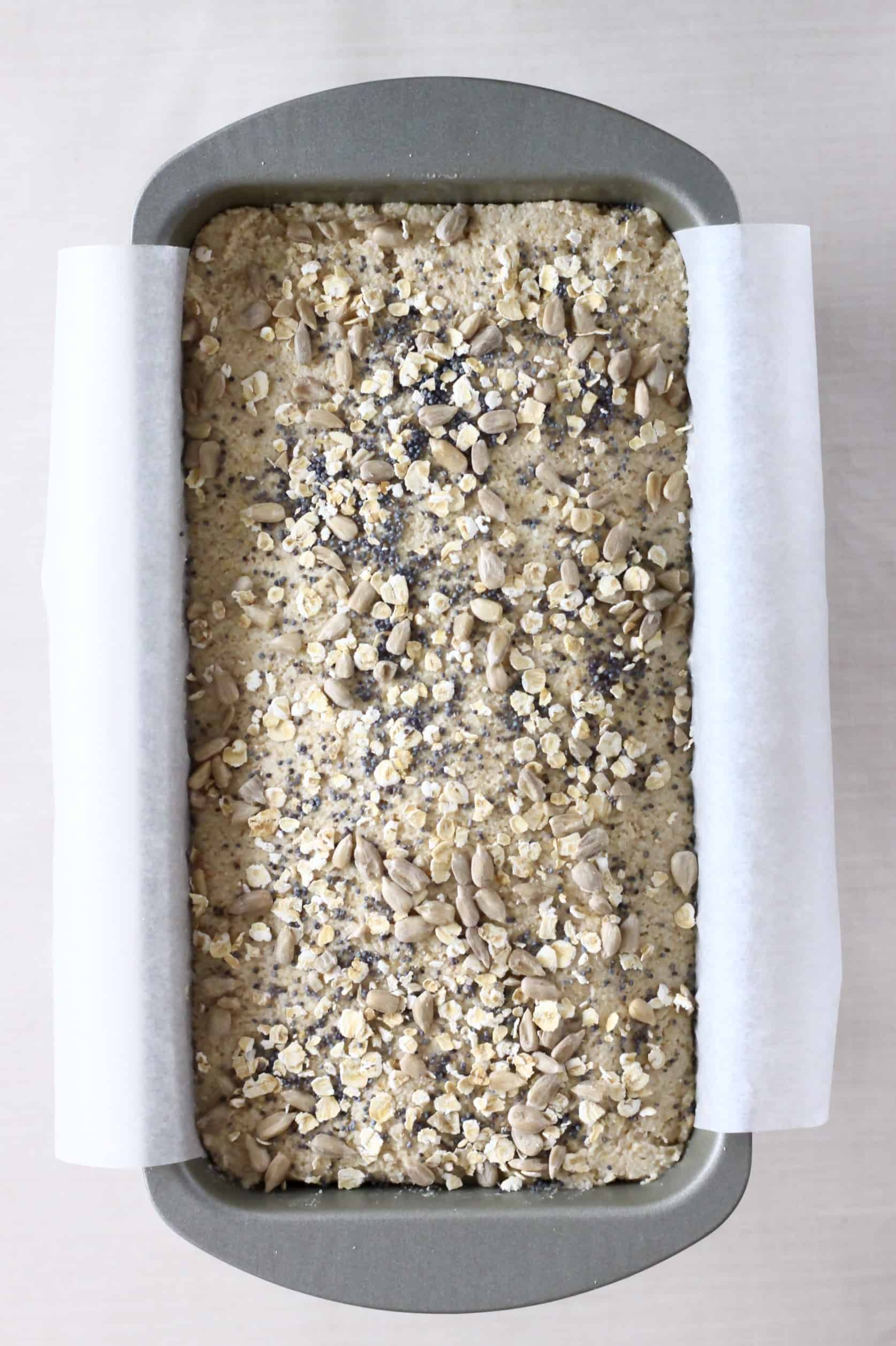 Oat flour bread dough topped with oats and seeds in a loaf tin