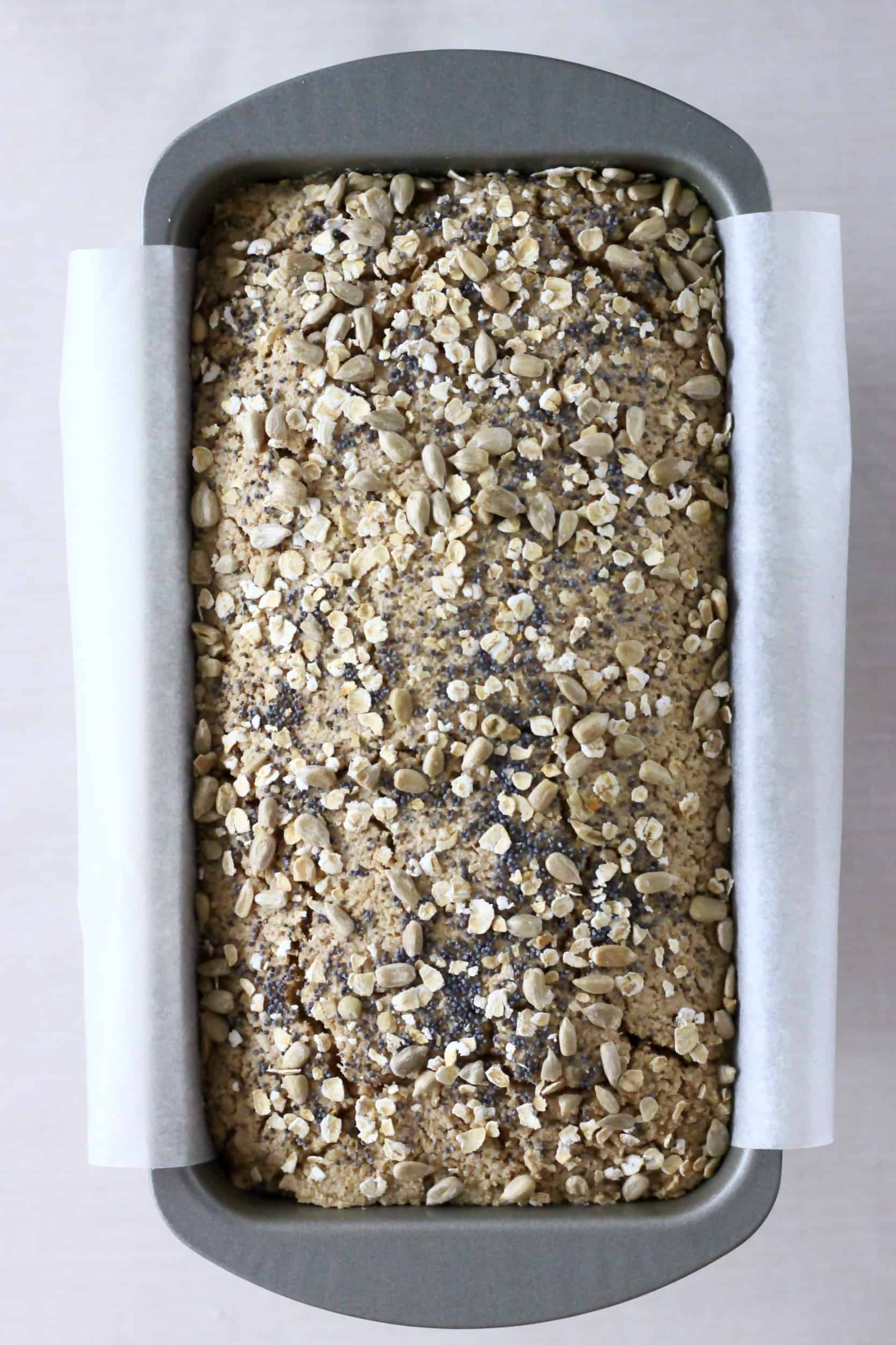 Oat flour bread topped with oats and seeds in a loaf tin