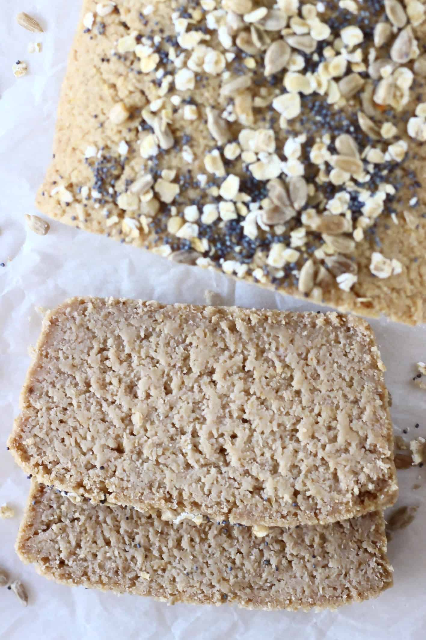 A loaf of oat flour bread topped with oats and seeds with two slices next to it
