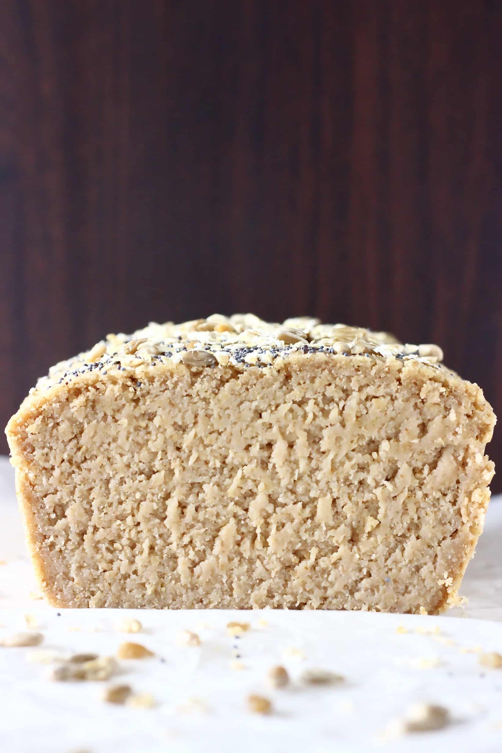 A sliced cross-section of a loaf of oat flour bread topped with oats and seeds