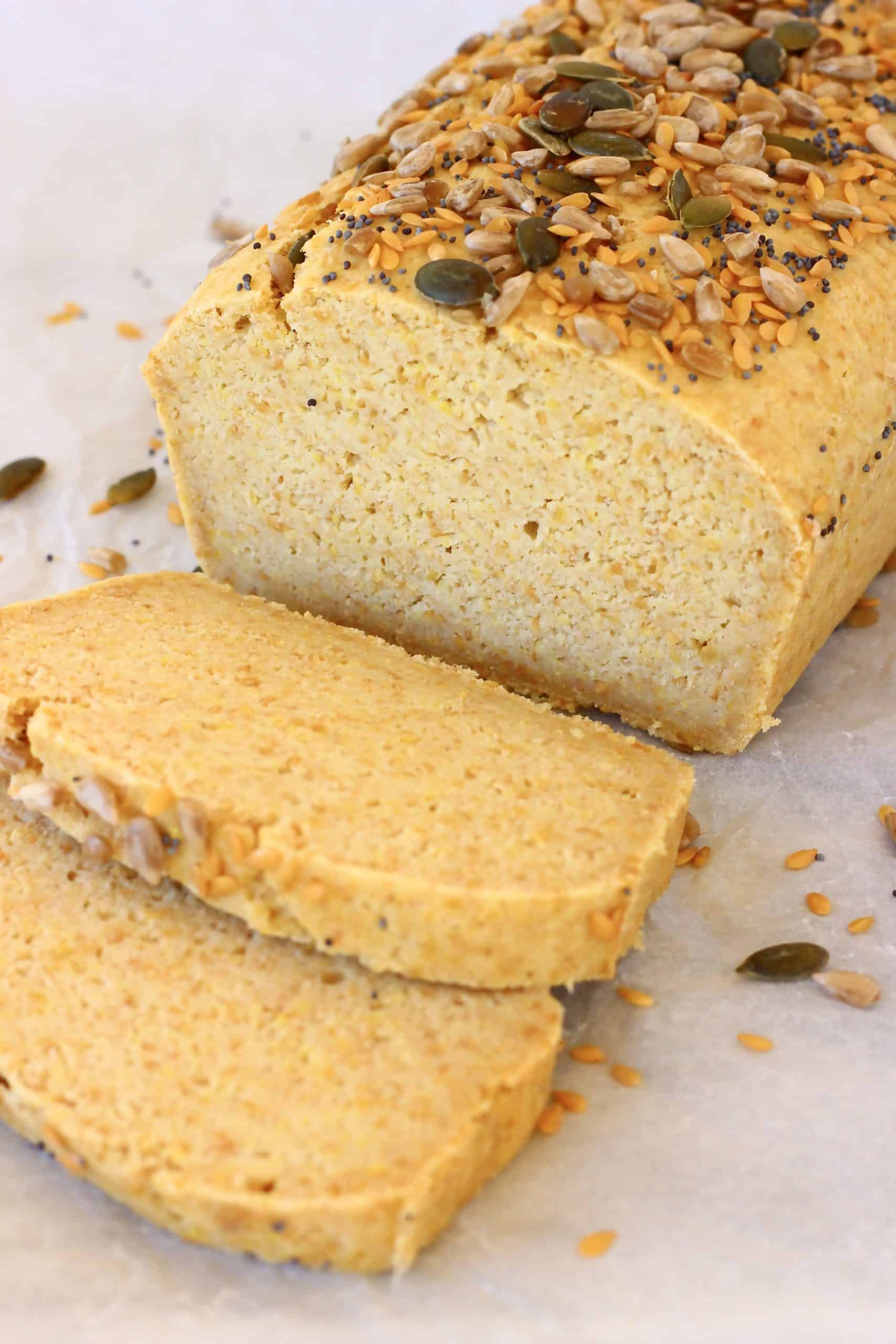 A loaf of flaxseed bread topped with seeds with two slices next to it