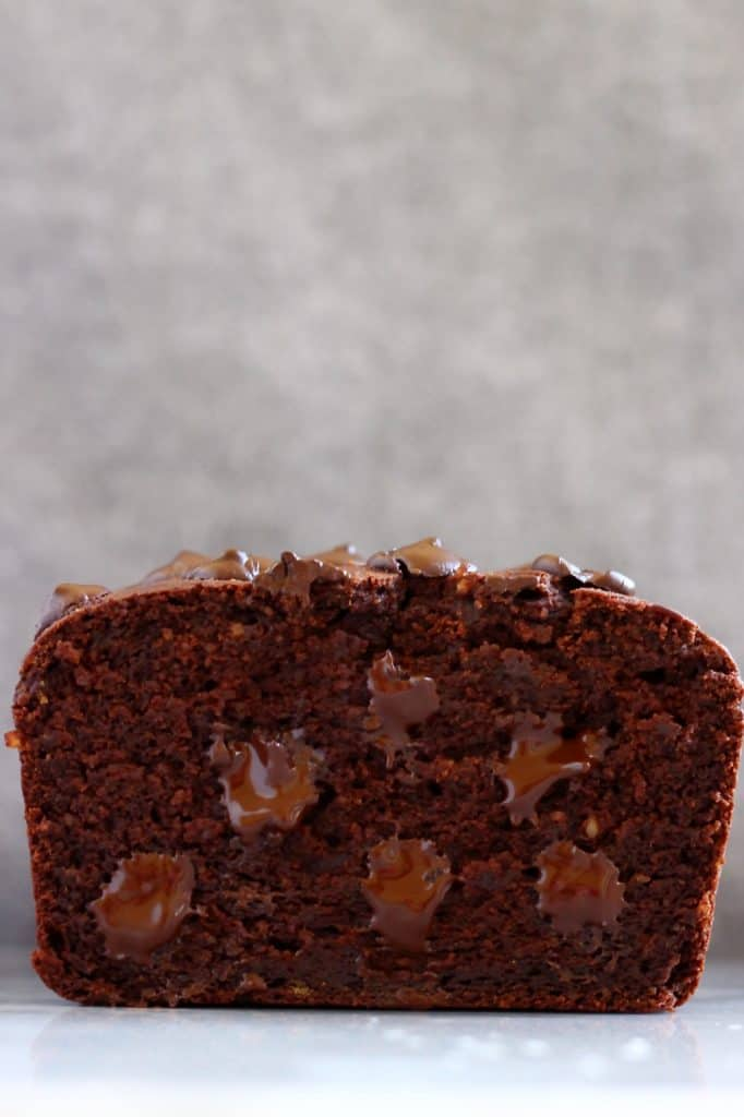 Sliced chocolate loaf cake with chocolate chips against a grey background