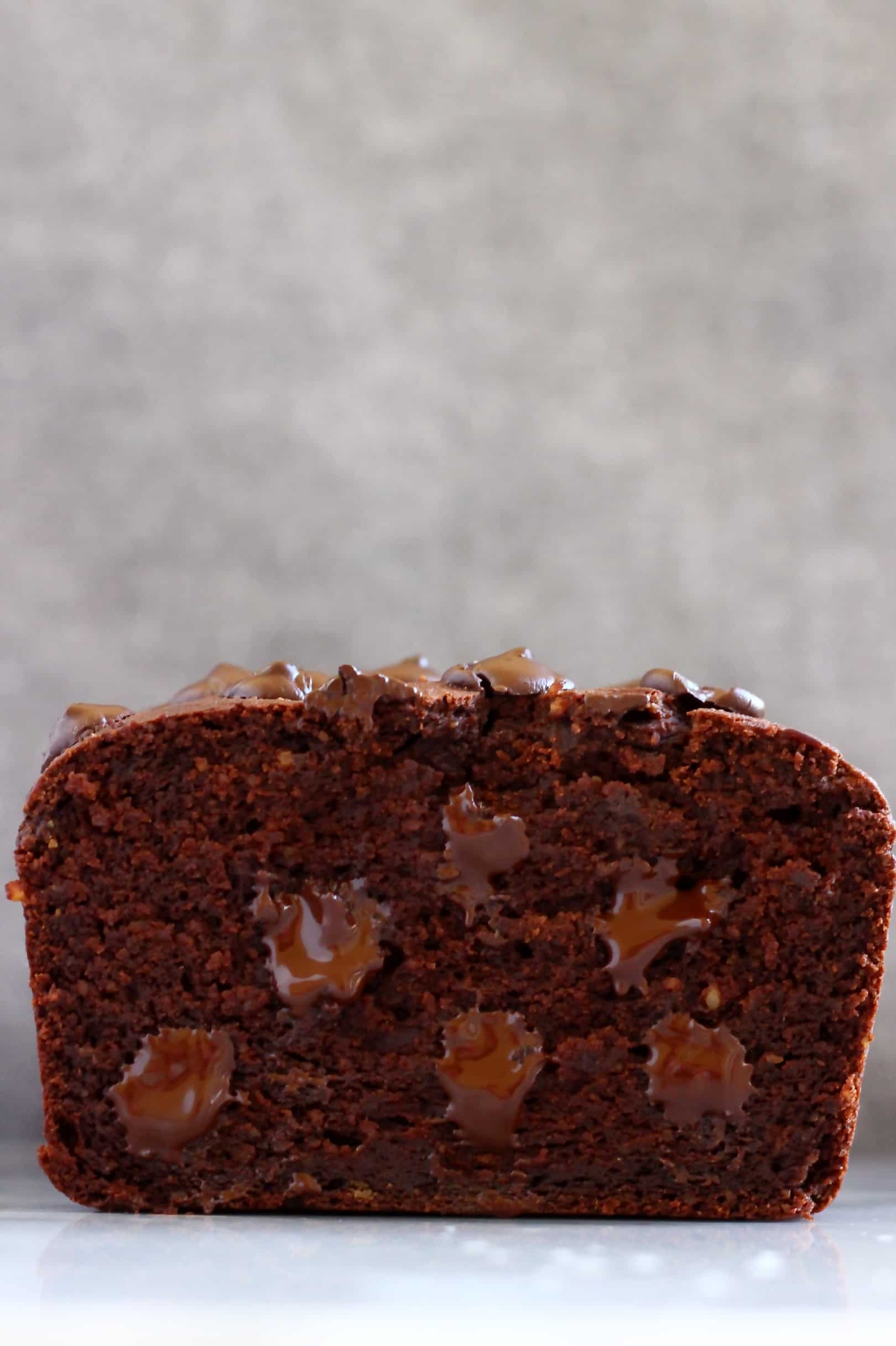 Sliced sweet potato chocolate loaf cake with chocolate chips against a grey background