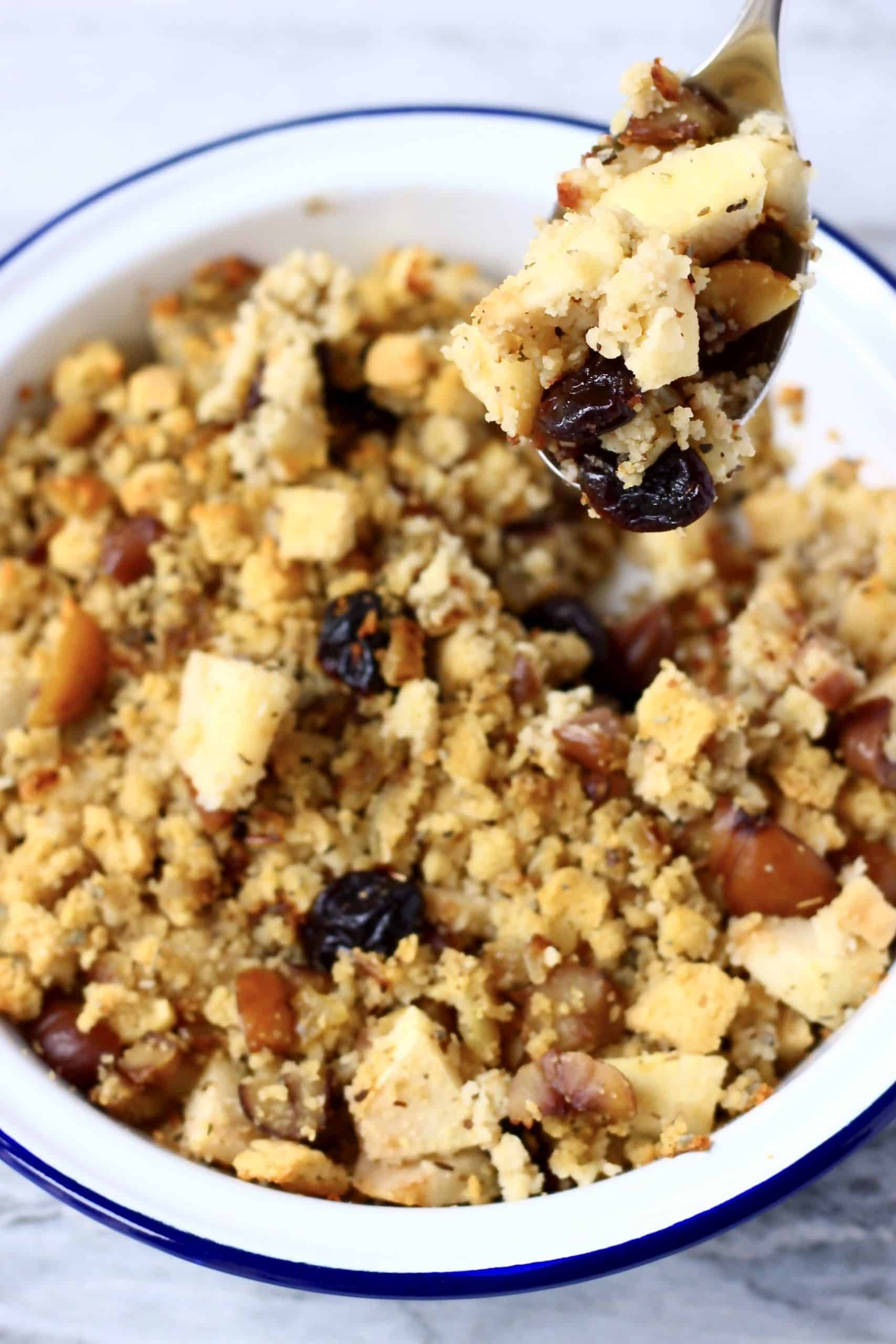 Stuffing with chestnuts, apple pieces and dried cherries in a white pie dish with a blue rim with a silver spoon holding up a mouthful of stuffing