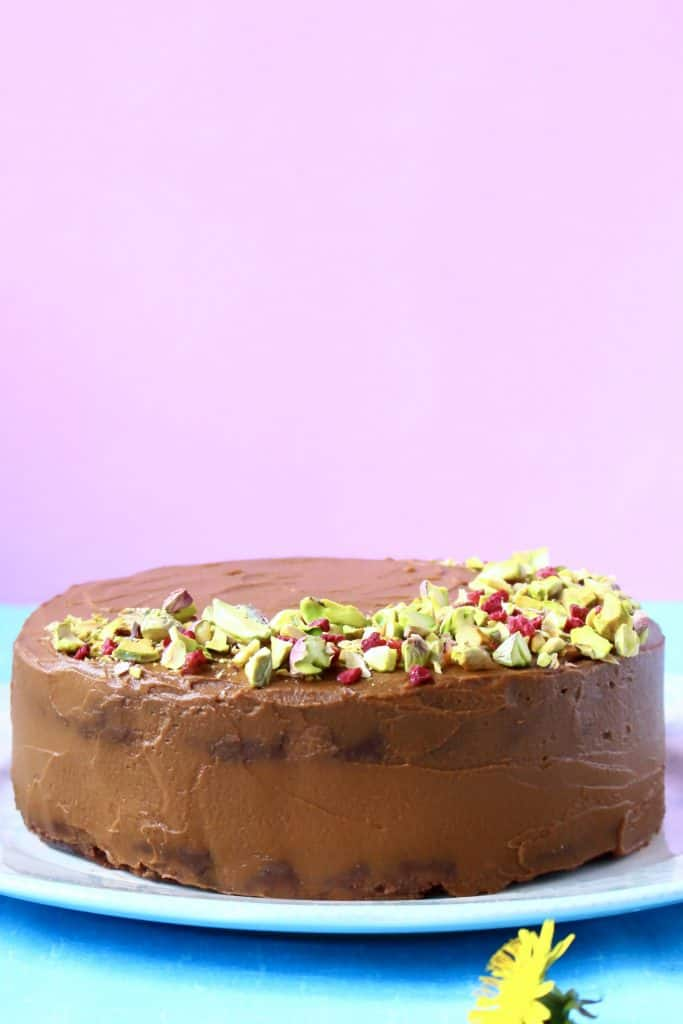 Chocolate truffle cake covered in chocolate frosting topped with chopped pistachios and freeze-dried raspberries