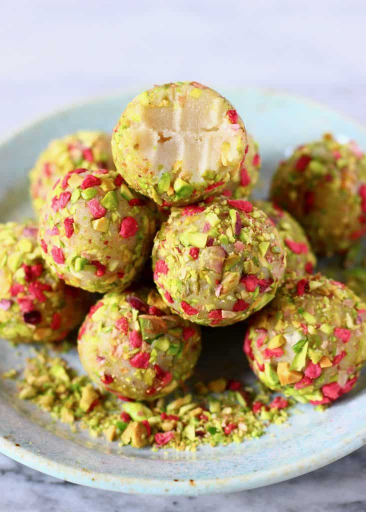 A pile of white chocolate truffles covered with chopped pistachios and freeze-dried raspberries with a bite taken out of one