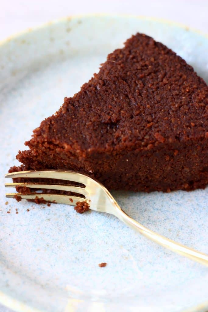 A slice of chocolate torte with a mouthful taken out of it