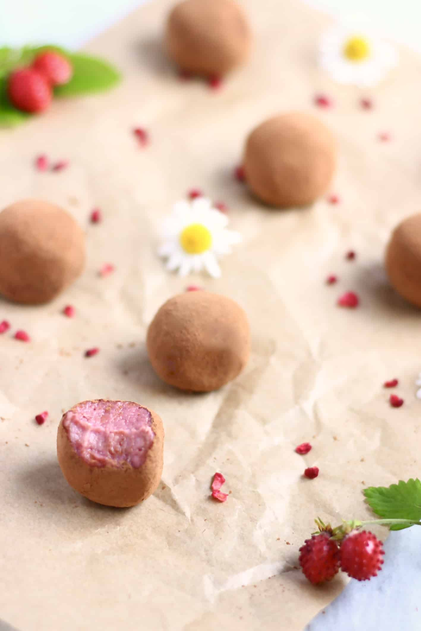 Six strawberry truffles covered in cocoa powder with a mouthful taken out of one