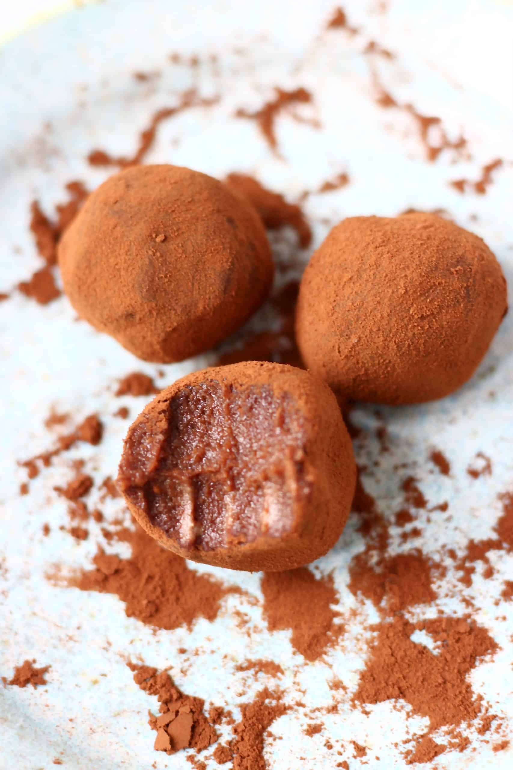 Three chocolate truffles dusted with cocoa powder with a bite taken out of one