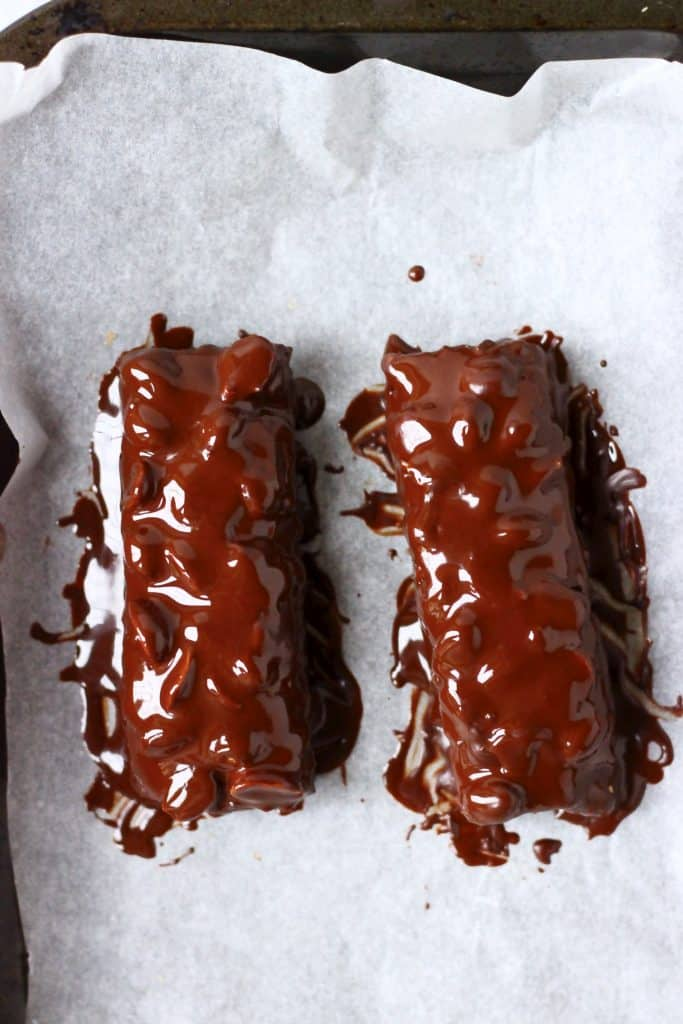 Two vegan snickers bars dipped in melted chocolate on a baking tray lined with paper