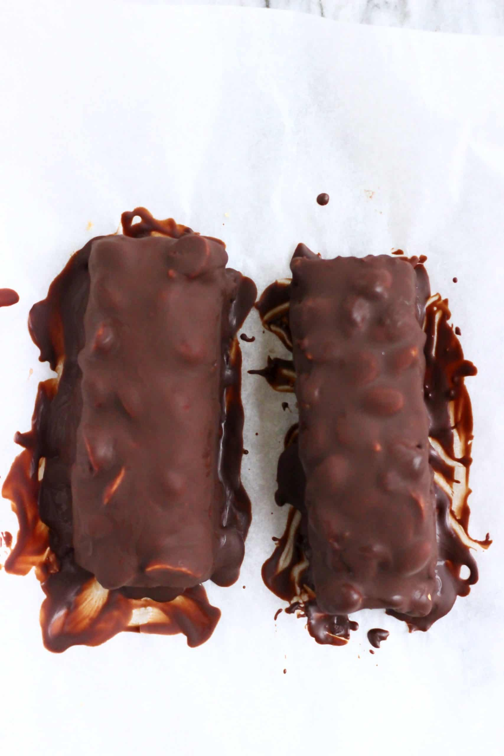 Two vegan snickers bars on a sheet of white baking paper