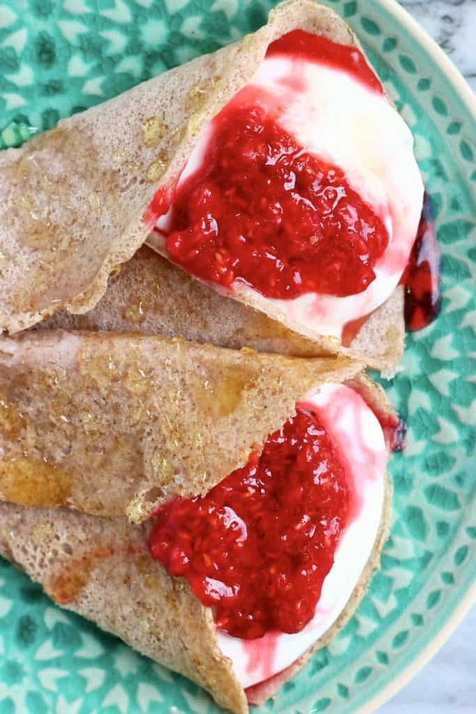Two buckwheat crepes filled with whipped cream and jam on a green plate