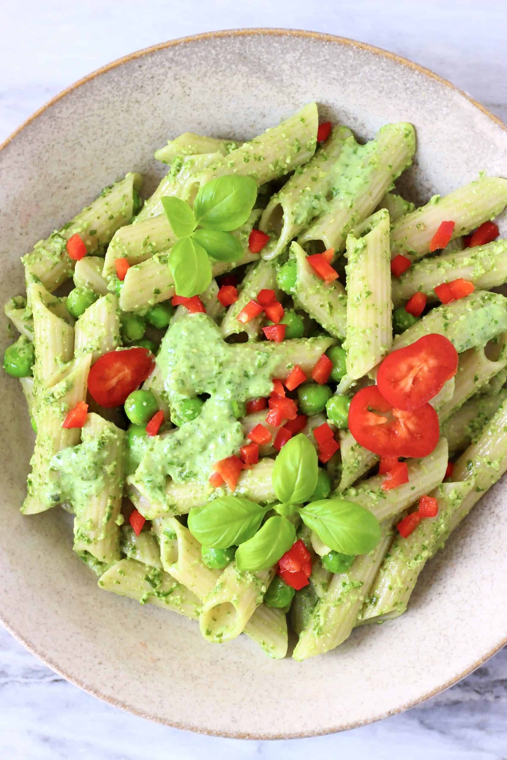 Penne pasta with pesto sauce, green peas and chopped red pepper in a beige bowl against a marble background