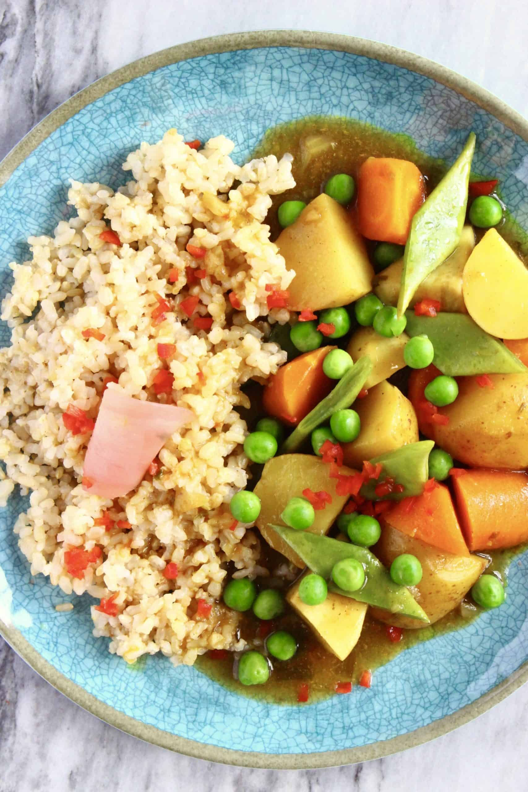 Japanese curry with potatoes, carrot and peas with brown rice on a blue plate