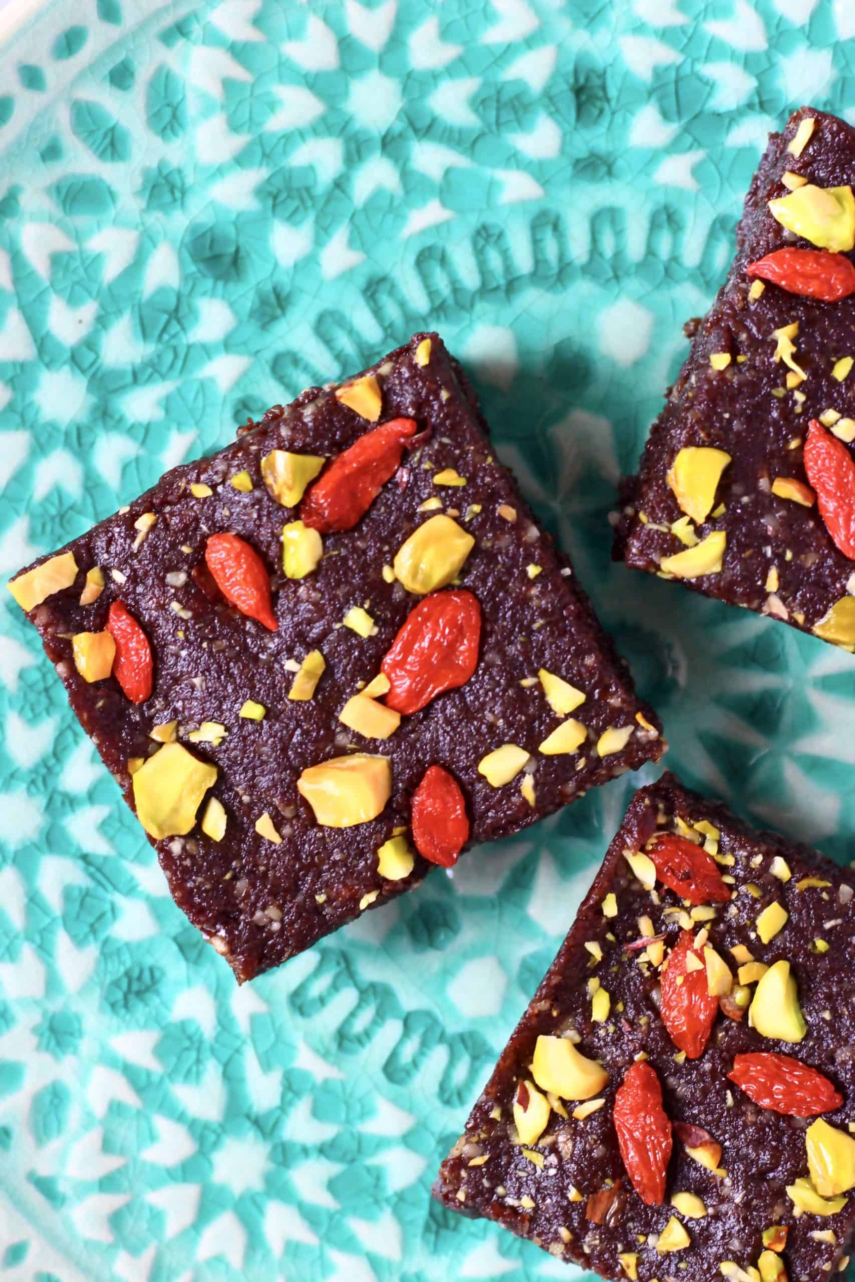 Three no-bake brownies topped with goji berries and pistachios on a green plate