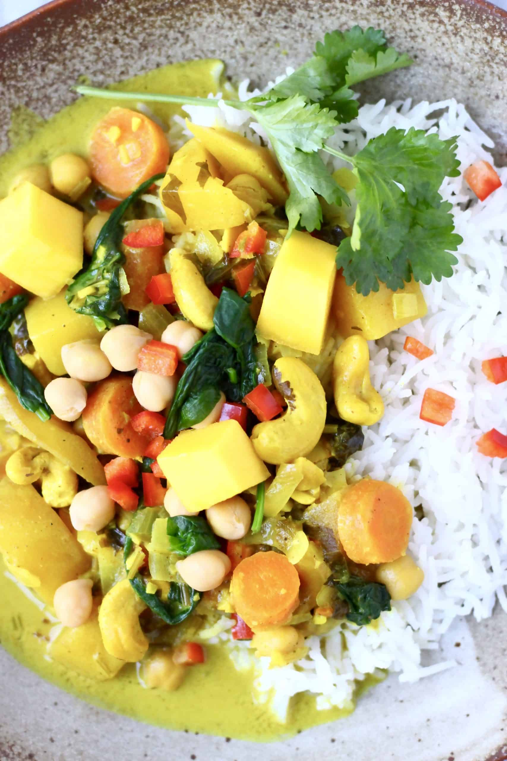 Chickpea mango cashew coconut curry with rice on a brown plate