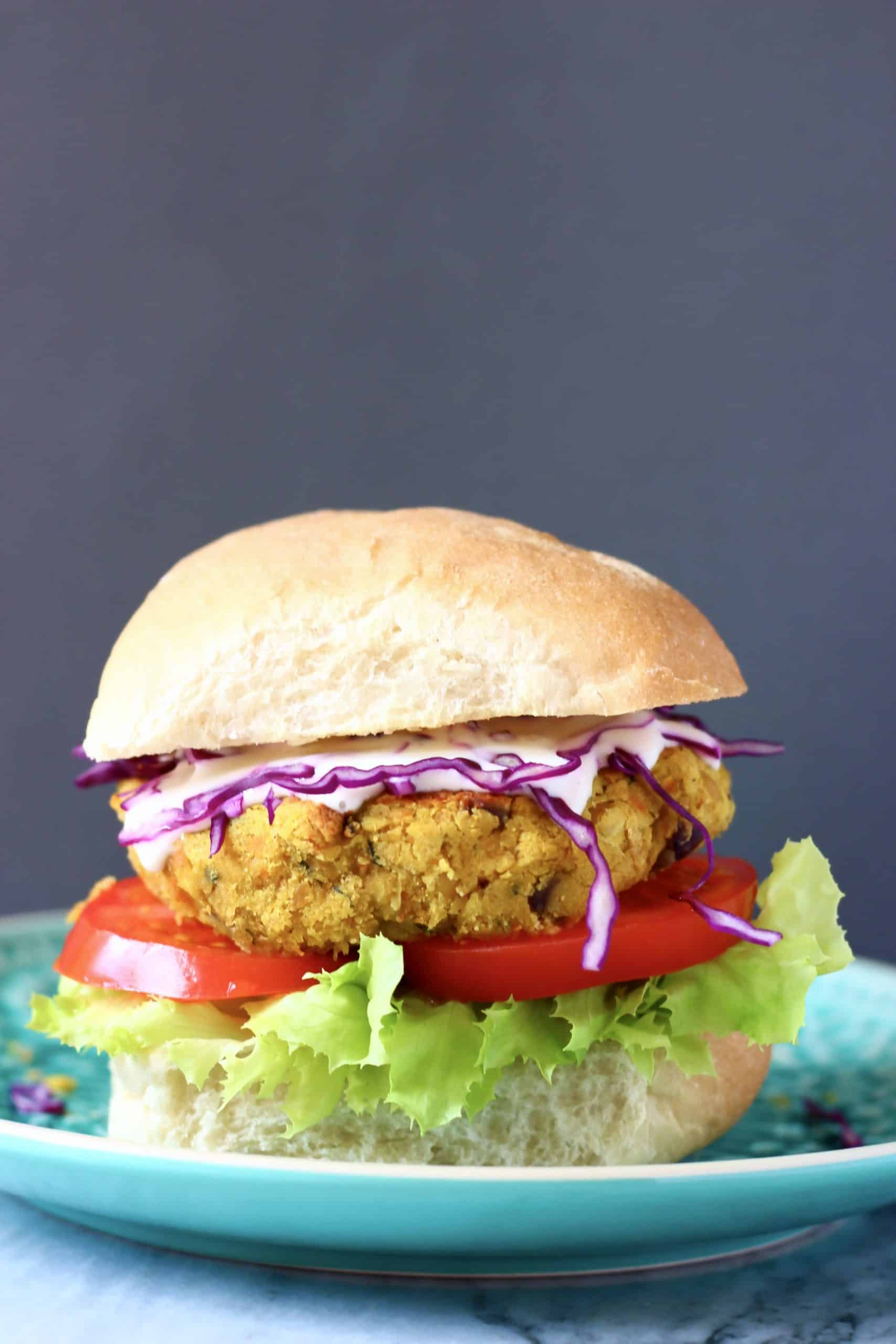 Curried chickpea burger with salad on a blue plate