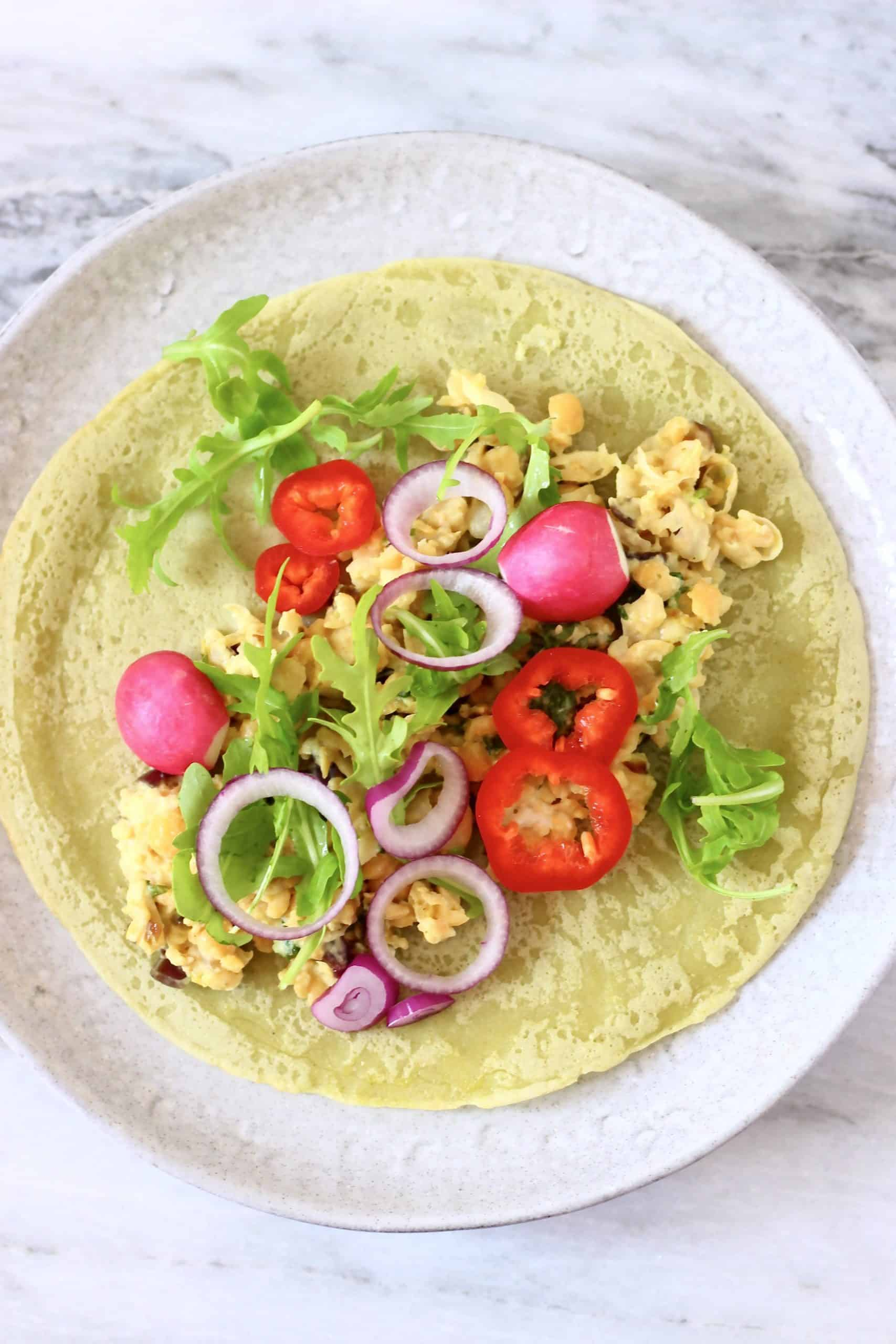 A green gluten-free vegan wrap topped with beans and salad on a white plate