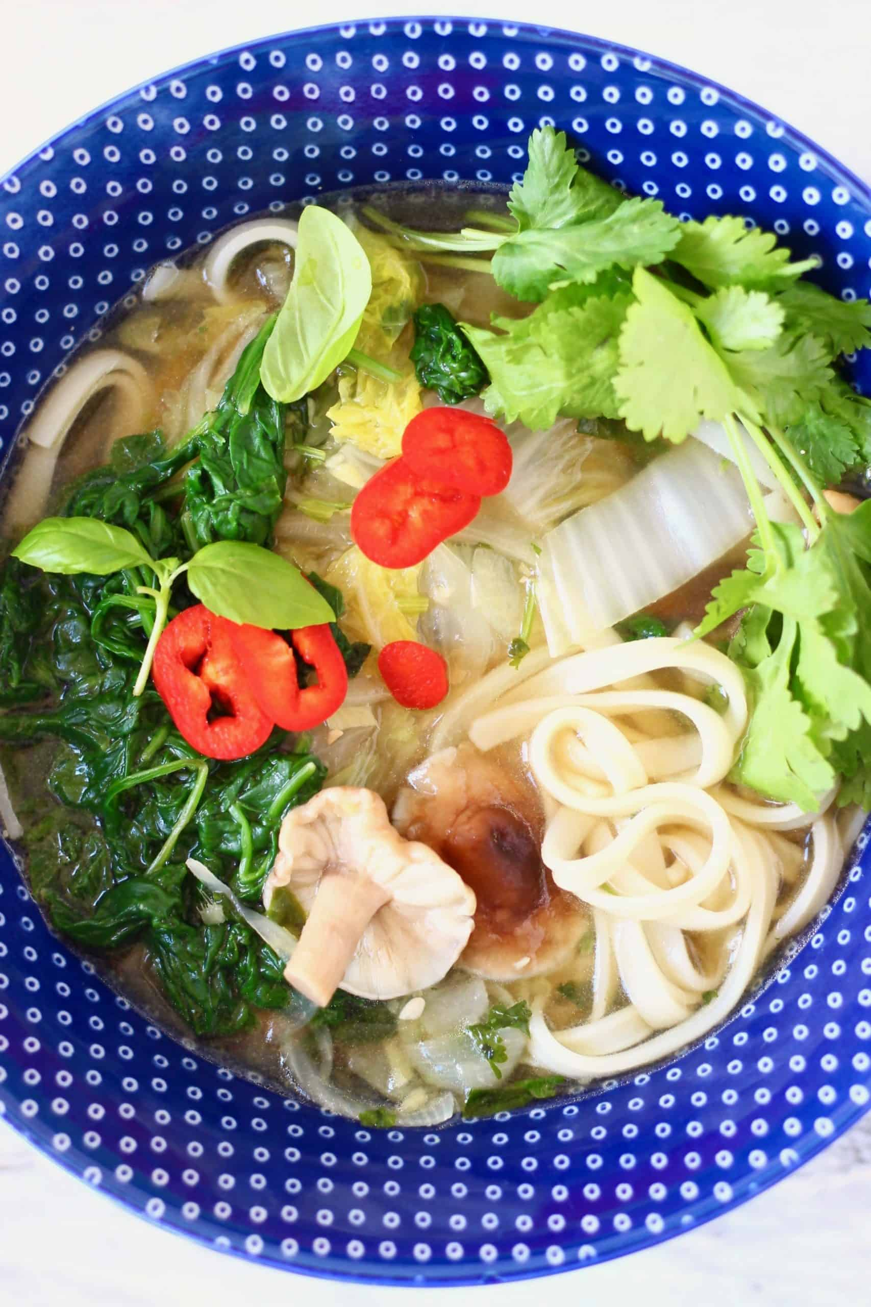 Vegan pho with vegetables in a blue bowl