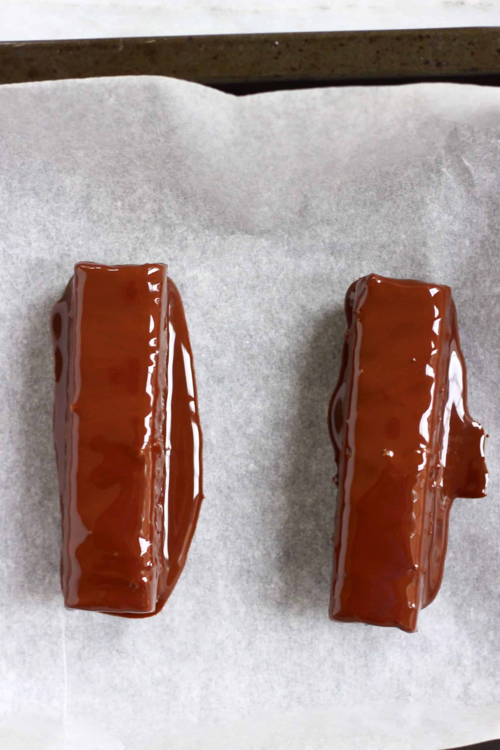 Two vegan twix bars dipped in melted chocolate on a tray lined with baking paper