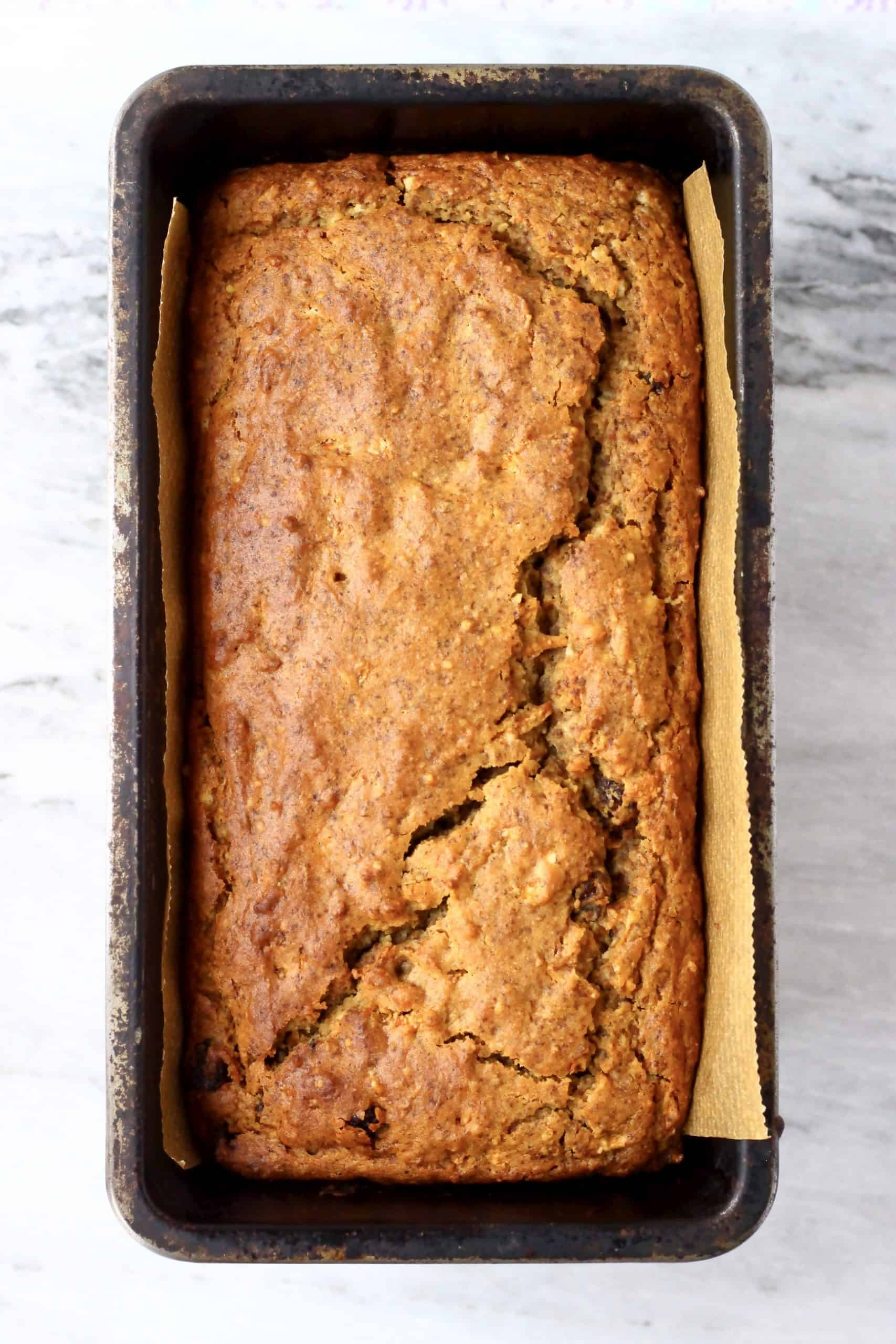 A loaf of vegan carrot bread in a loaf tin lined with baking paper