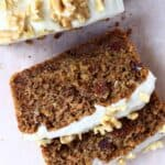 Two slices of vegan carrot bread topped with frosting and walnuts