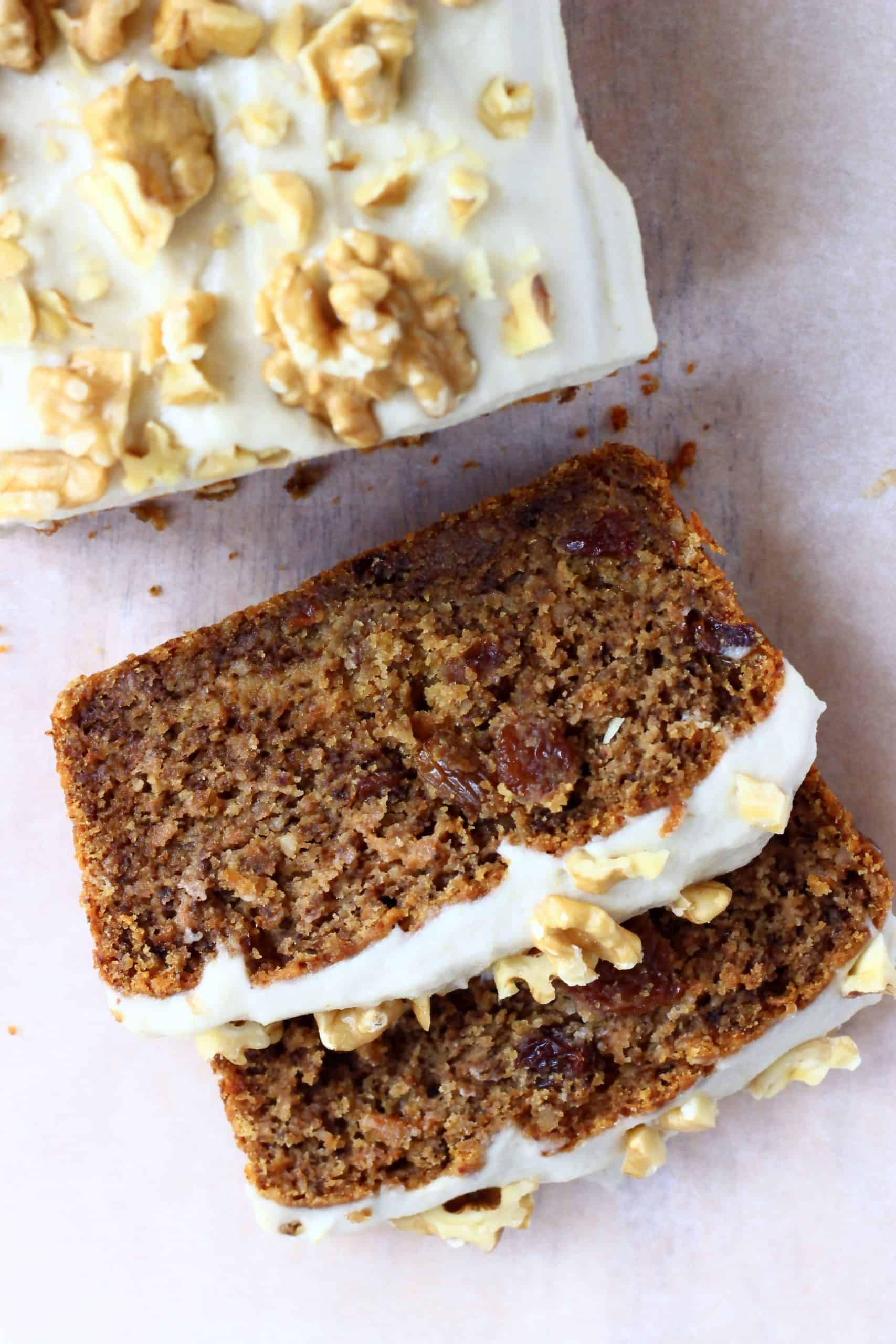 A loaf of vegan carrot bread topped with frosting and walnuts with two slices next to it
