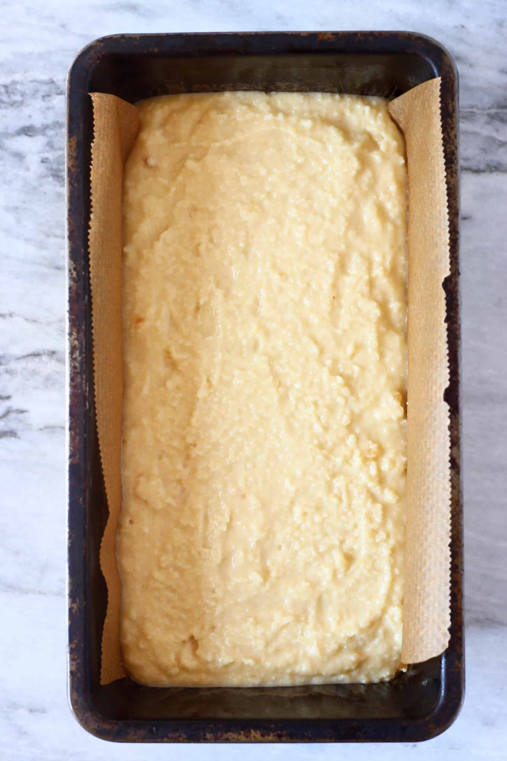 Raw vegan orange bread batter in a loaf tin lined with baking paper