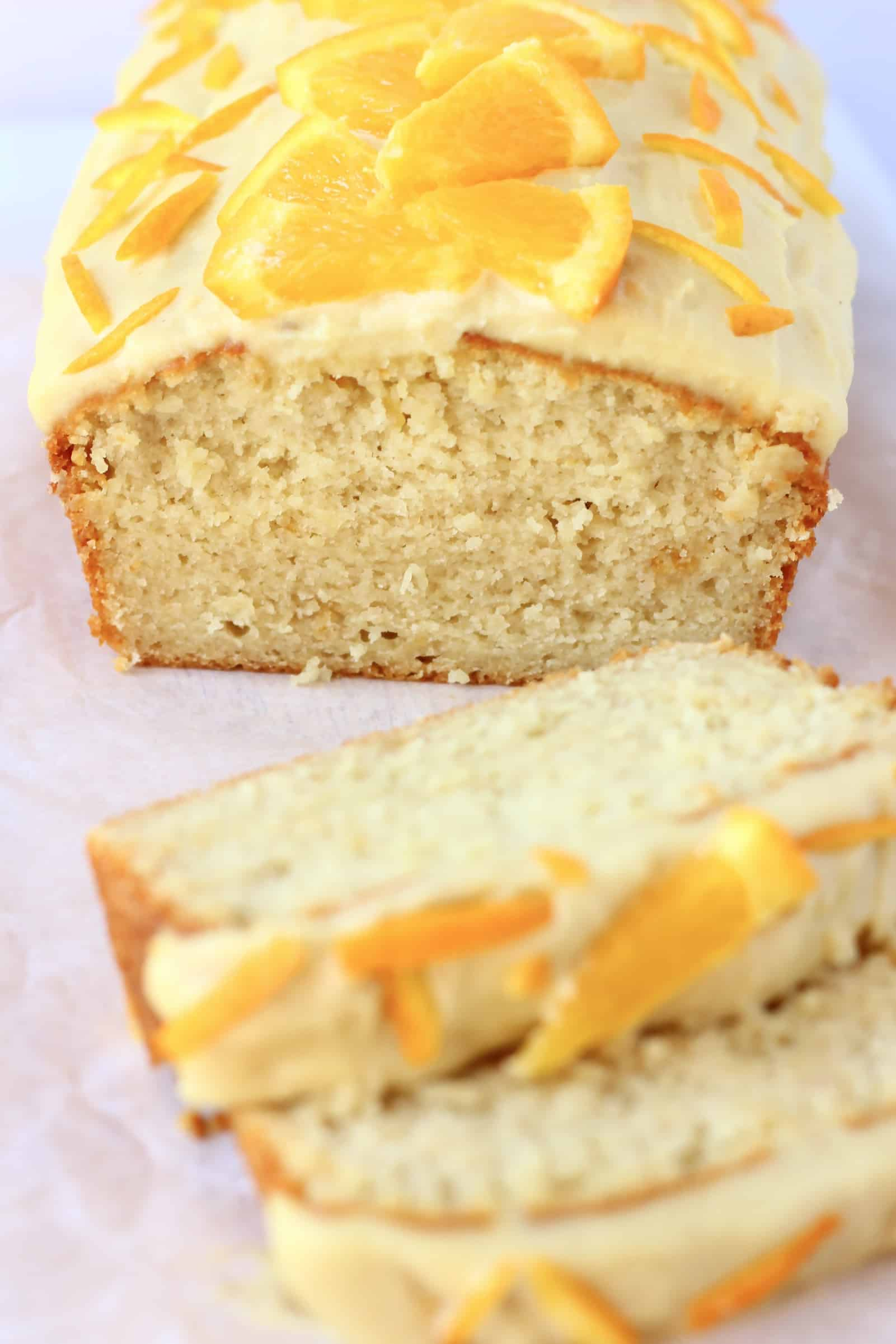 A loaf of vegan orange bread topped with frosting and orange slices with two slices next to it