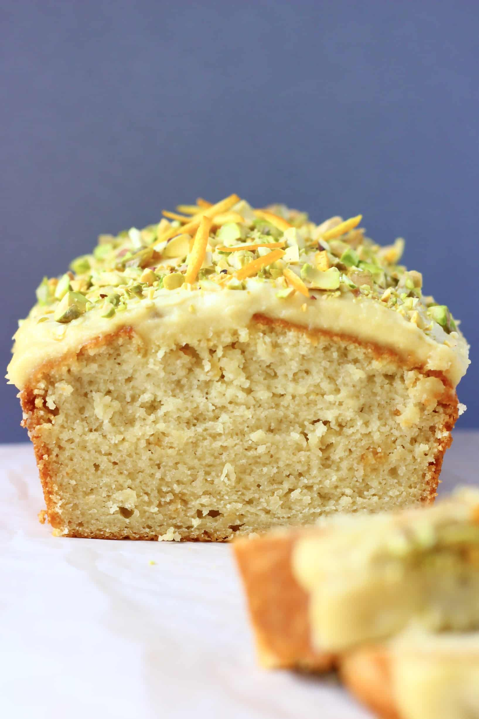 A loaf of vegan orange bread topped with frosting and chopped pistachios with two slices next to it