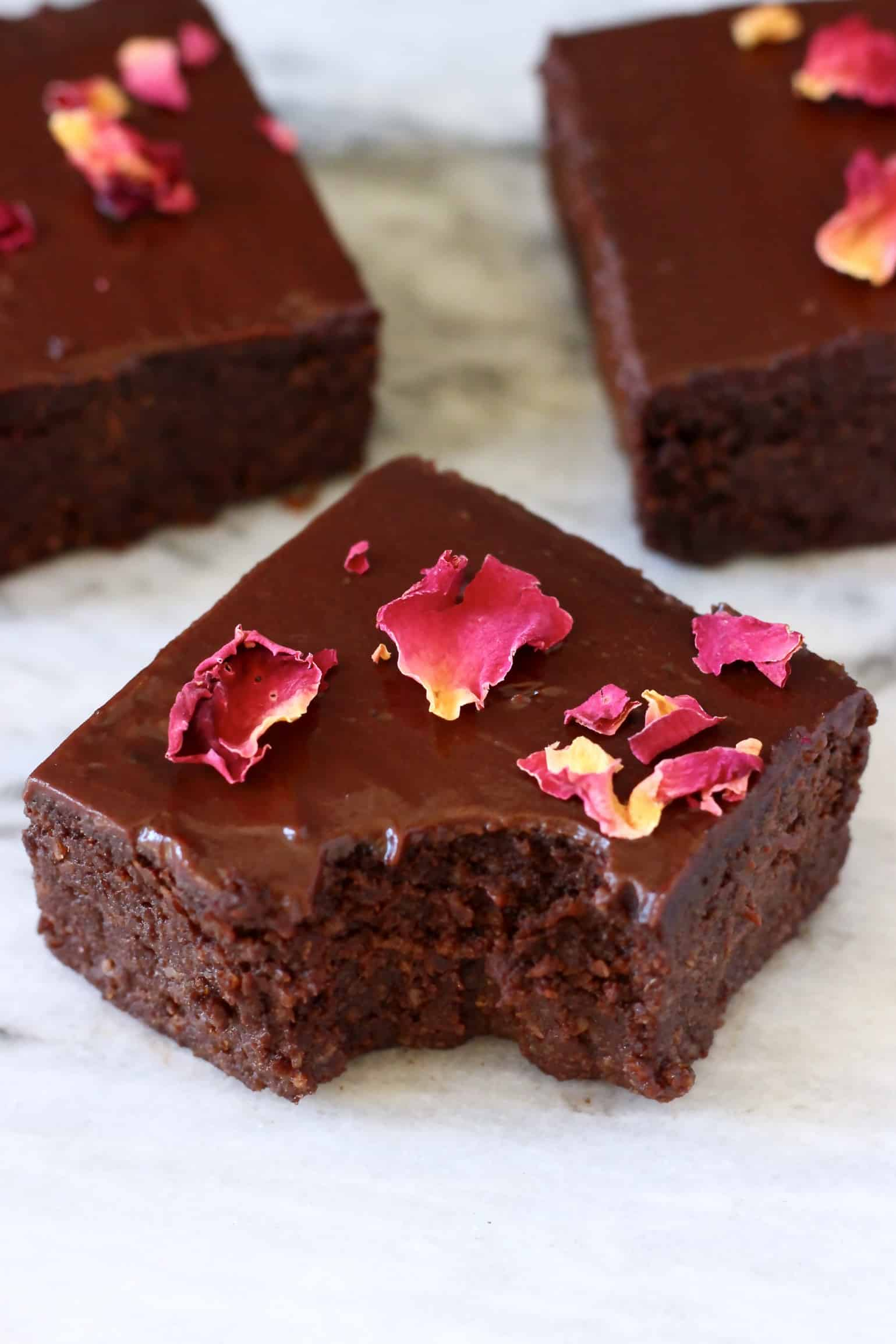 Three avocado brownies with chocolate frosting and rose petals with a bite taken out of one